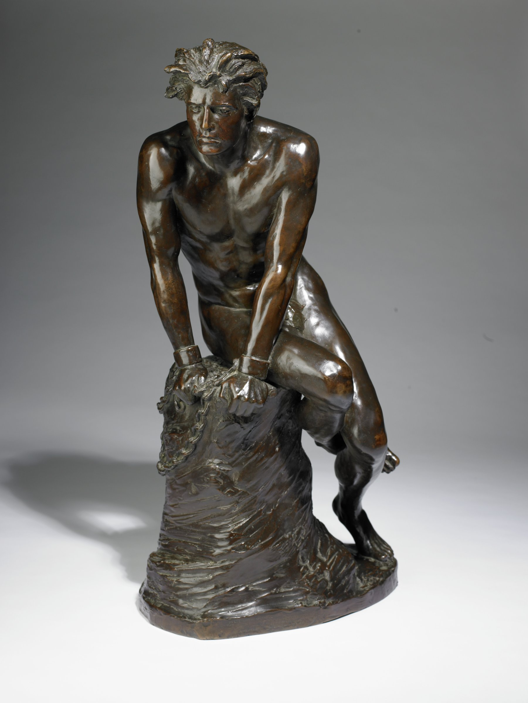 This bronze sculpture represents a nude man seated on a rock with chains on his wrists.