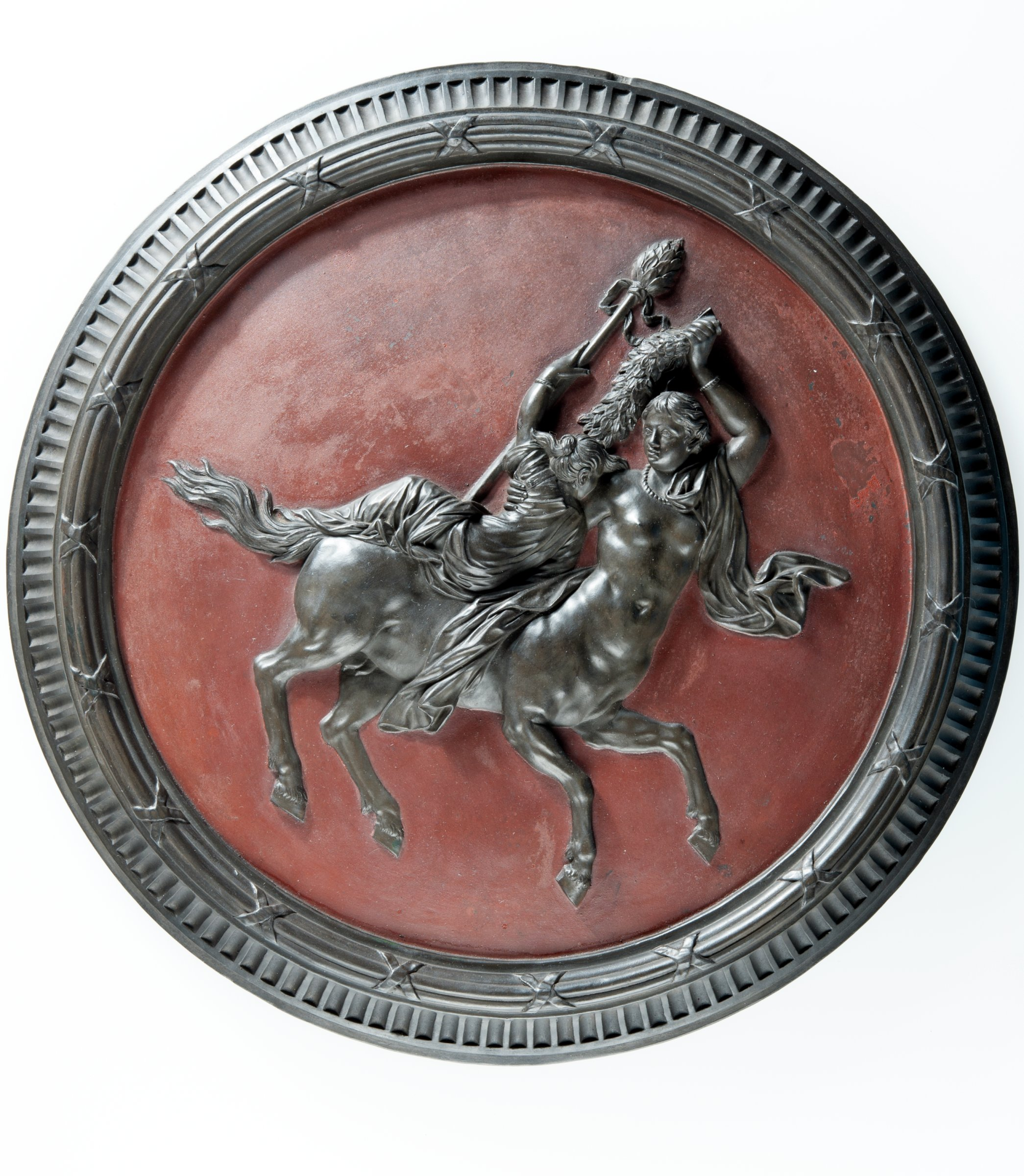 Large round, self-framed plaque of black basalt with an image of a centaur and a nymph, or maenad, against a red encaustic ground.