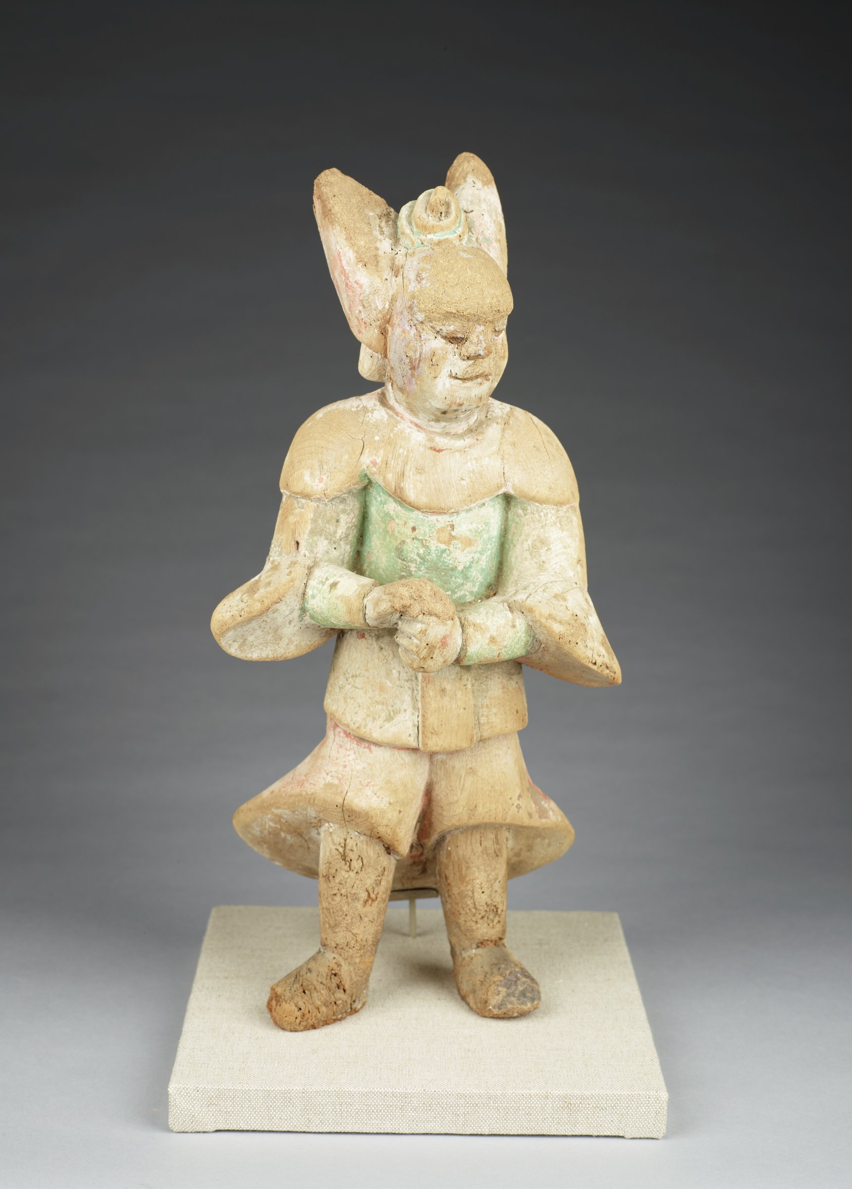 This stout standing figure retains trases of green and white paint. His legs splayed sighlyt to support his stocky aspect, his arms are bent at the elbows with the proper right hand resting on top of the the left fist. His trousers and sleeves are flared in a dynamic movement. His upstanding hairstyle is typical of fierce, protective figures and a small coiled snake rests between his locks. His head is turned to the proper left. He wears a cloud colar and high boots.