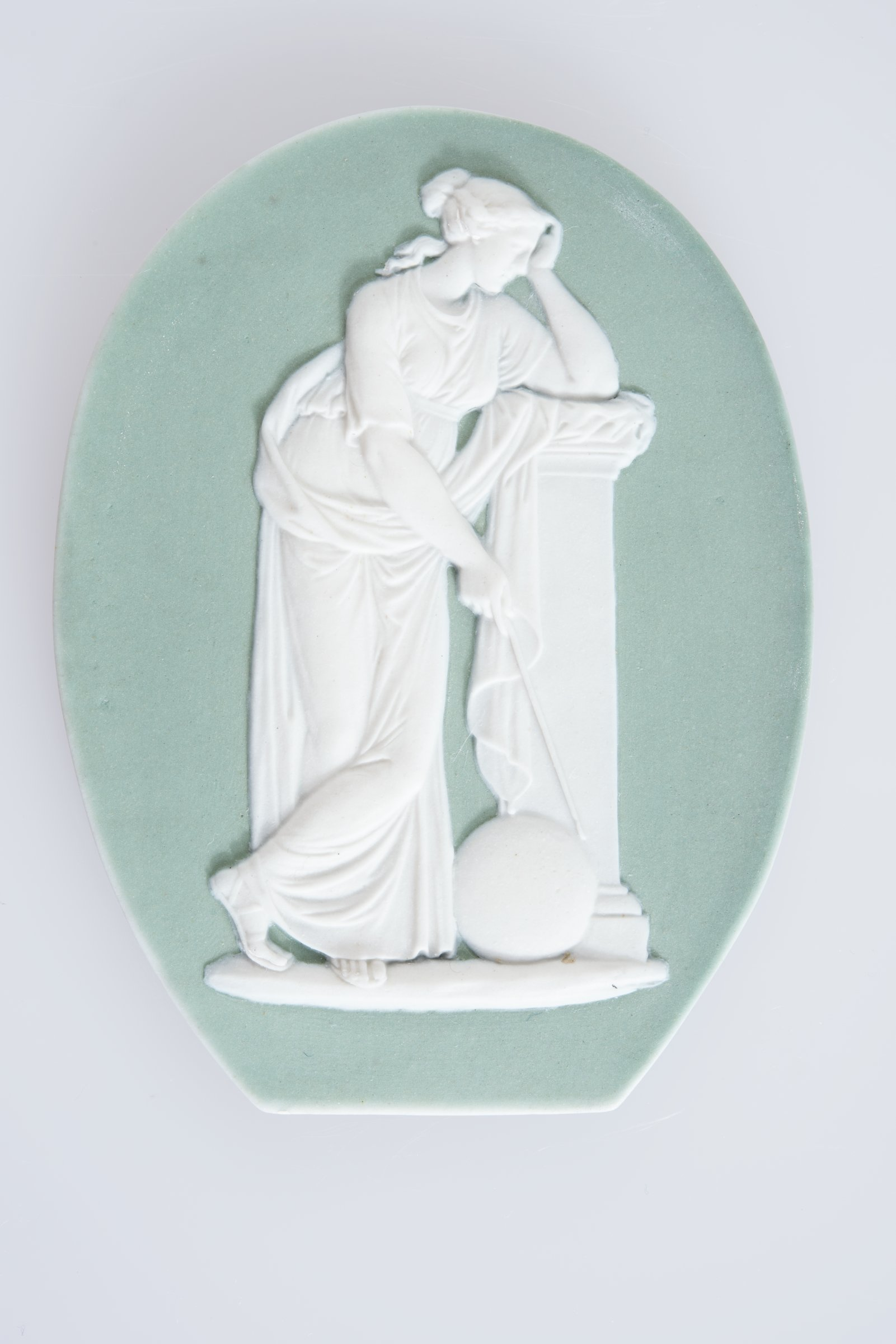 Small, oval plaque (truncated at the lower edge) of white jasper with green jasper dip and white relief decoration of the Muse Urania who presided over astronomy, and often holds a compass used by astronomers in her hand, standing in full figure next to a pedestal with a globe at her feet.