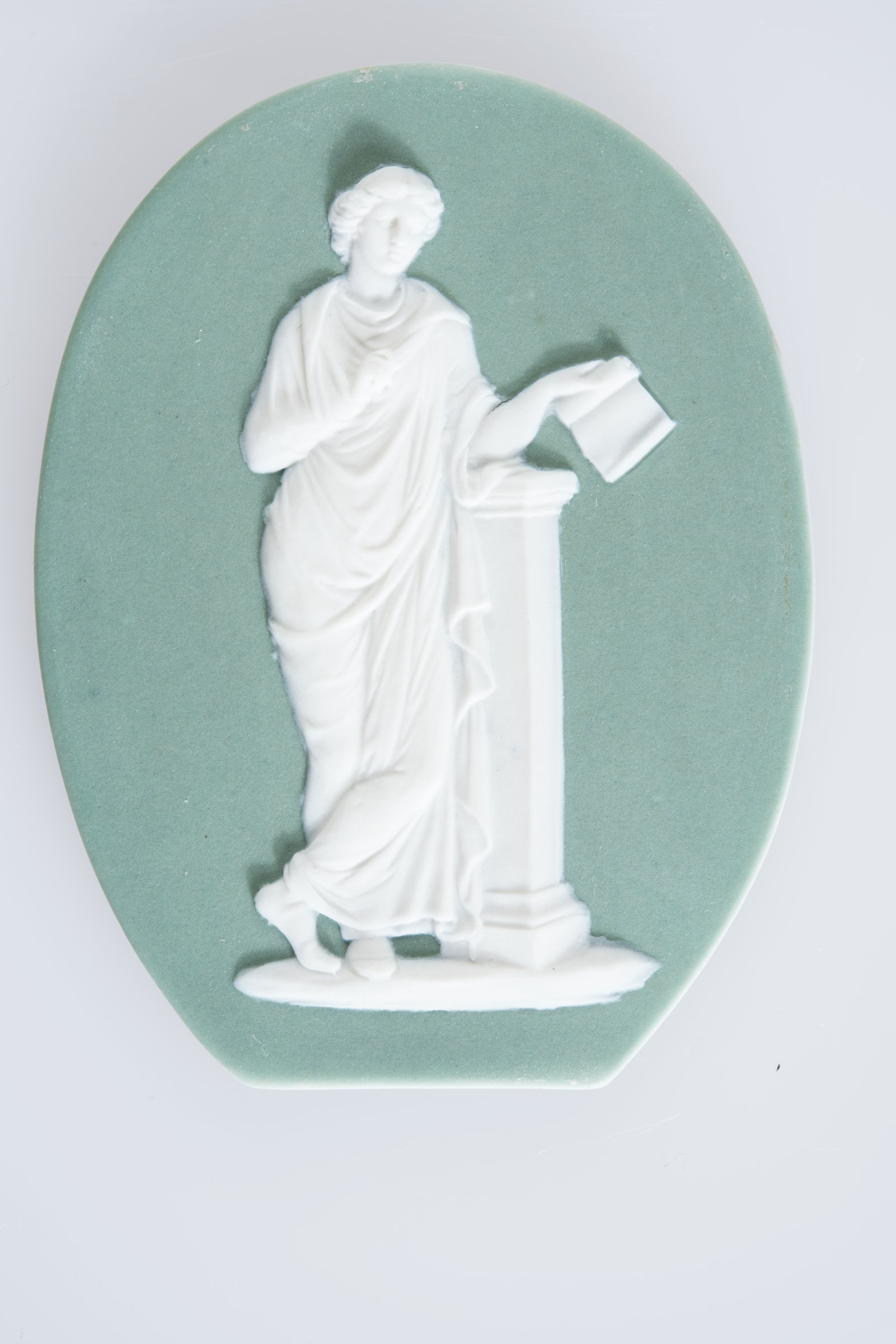 Small, oval plaque (truncated at the lower edge) of white jasper with green jasper dip and white relief decoration of the Muse Calliope, who presided over eloquence and heroic poetry, and often holds a tablet or roll of paper and stylus, standing in full figure next to a pedestal.