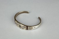 Cast silver band bracelet, open at underside of wrist, inlaid with ebony; engraved and punched linear and repeating geometric patterns