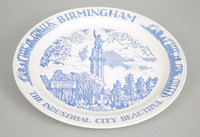 Souvenir plate with blue transfer-printed decoration. Border reading BIRMINGHAM / THE INDUSTRIAL CITY BEAUTIFUL (top and bottom), with industrial skyline frieze (left and right). At center of plate, full-length view of Vulcan on pedestal with banner caption at left:  WHERE VULCAN, / THE MIGHTY MAN / OF IRON, STANDS