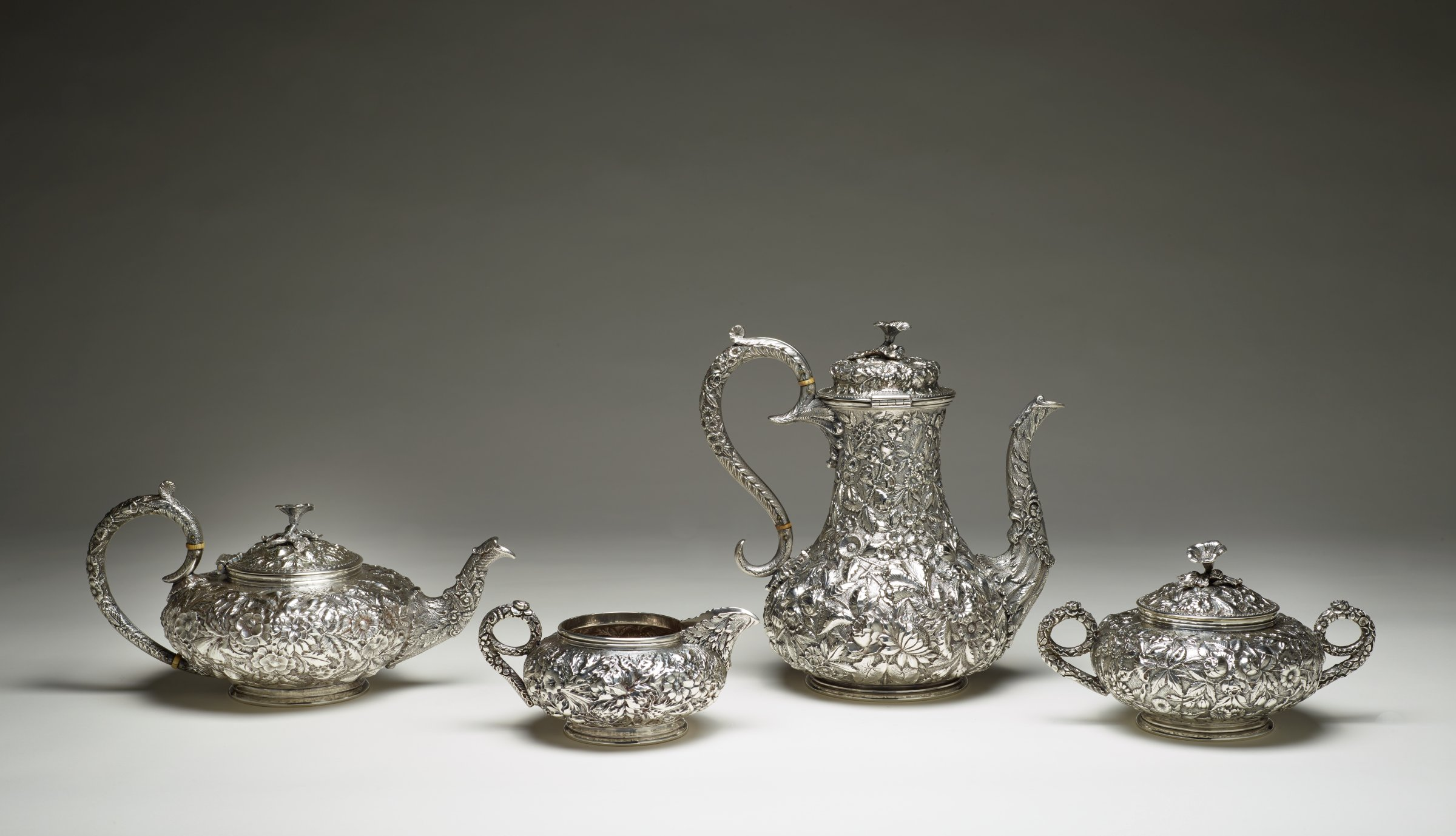 """Coffee and tea service consisting of (.1) coffee pot, (.2) teapot, (.3) creamer, and (.4a-b) covered sugar, each completely covered with a repoussé pattern of leaves and flowers in the Rococo-revival style, the lidded coffee pot of pear shape with curved spout, S-scroll handle insulated with ivory, domed lid and flower finial, the lidded teapot globular with curved spout, C-scroll handle insulated with ivory, and flower finial, the creamer also globular with scrolled handle and beak-shaped spout, the covered sugar with two scrolled handles and flower finial, each piece on slender stepped foot and engraved on base with the initials """"GJH"""" for """"Gena Jones Holt"""""""