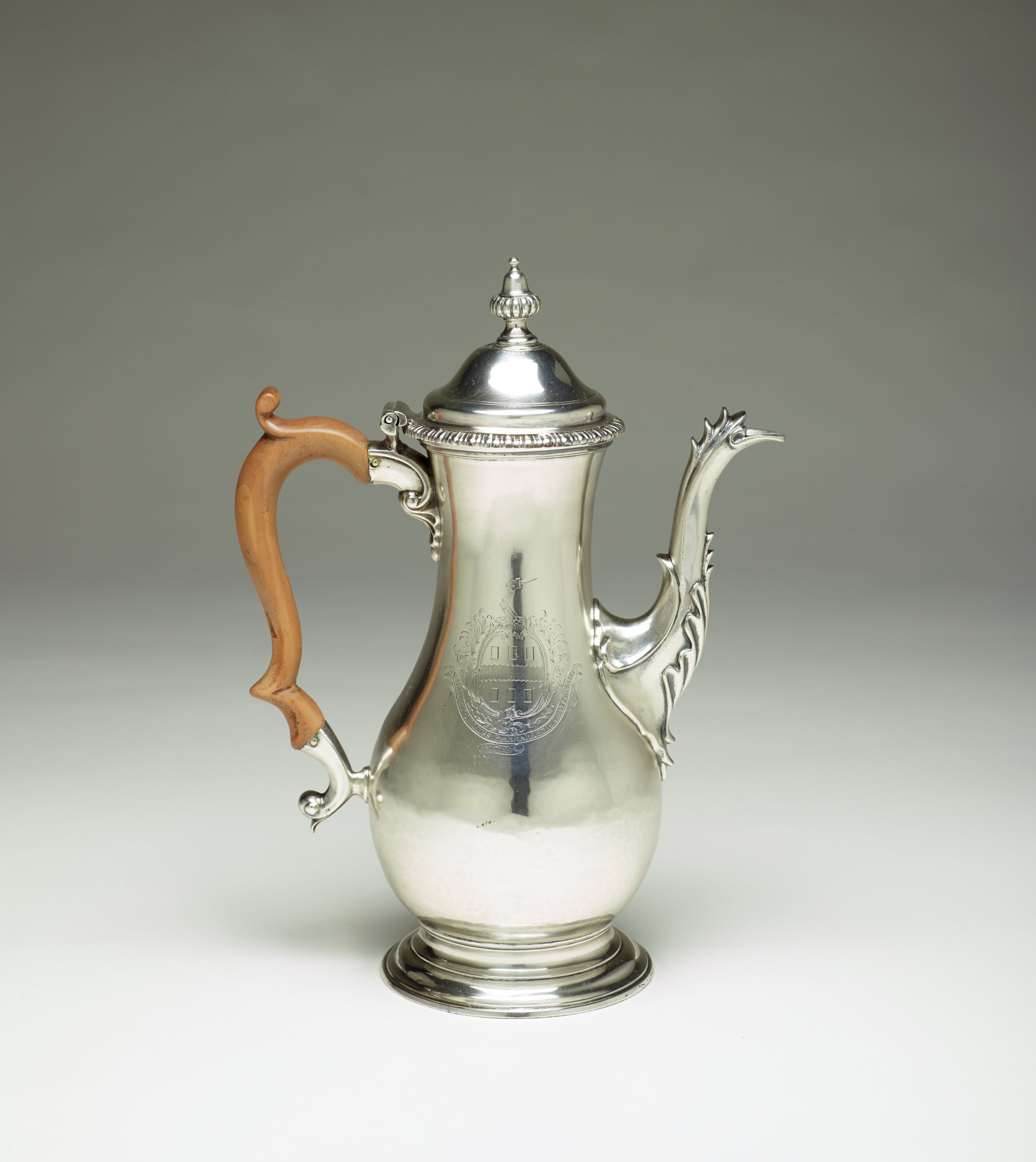 Tall silver coffeepot of elongated pear-shaped form on round, stepped foot, the elegantly curved spout decorated with stylized foliage, the wooden hand two modified C-scrolls with a tightly scrolled thumb rest, the hinged, domed lid with a band of gadrooning at the edge and with a fluted cap-shaped finial, one side of the main body engraved with a fictitious coat of arms above a banner that reads, IN MEMORY OF MISS BARBARA KIRKHAM OB: 10 DEC: 1769