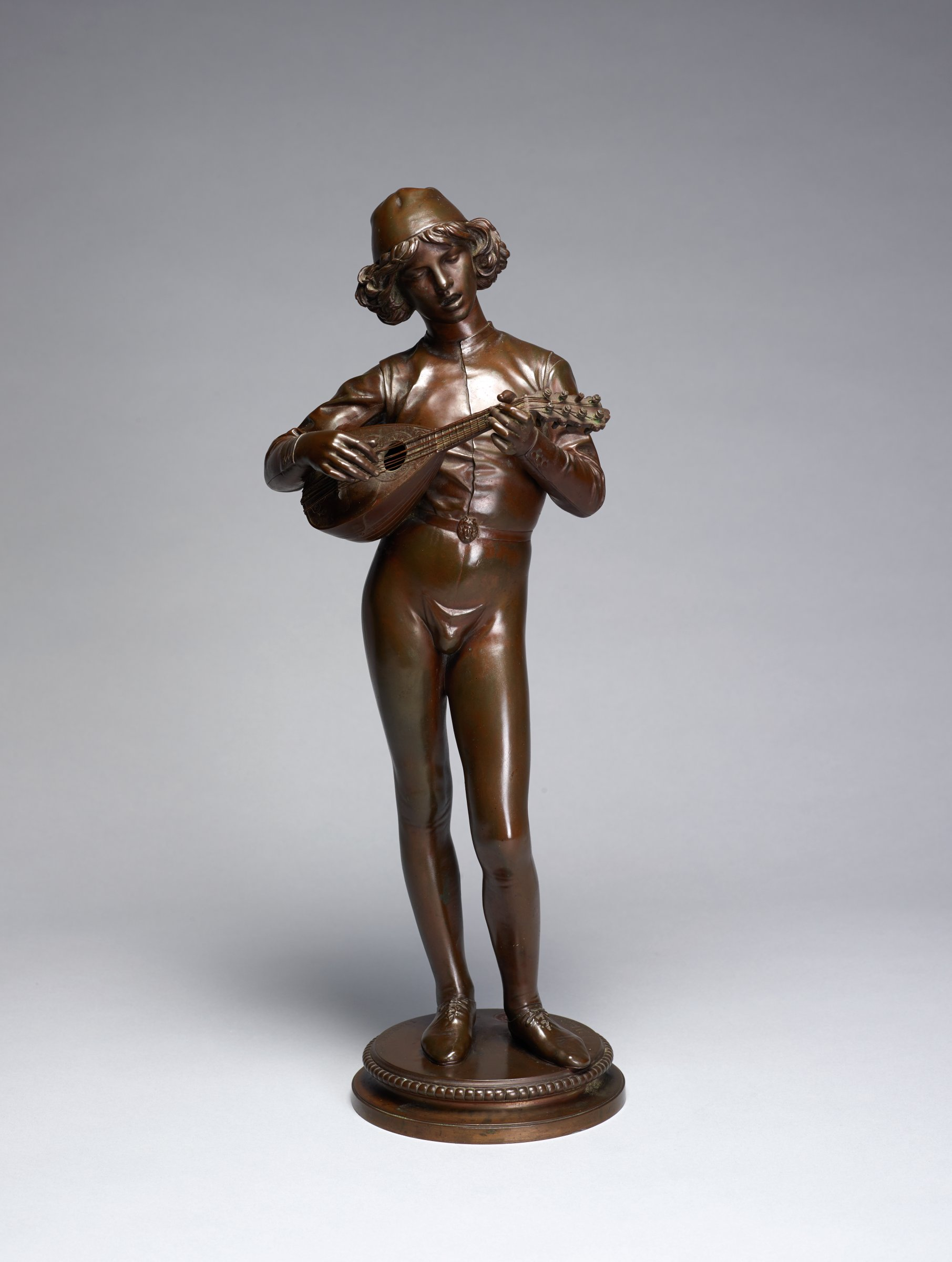 A young man sings and plays a mandolin. He stands with his weight shifted to his proper left leg. This sculpture is copied from a 15th century sculpture.