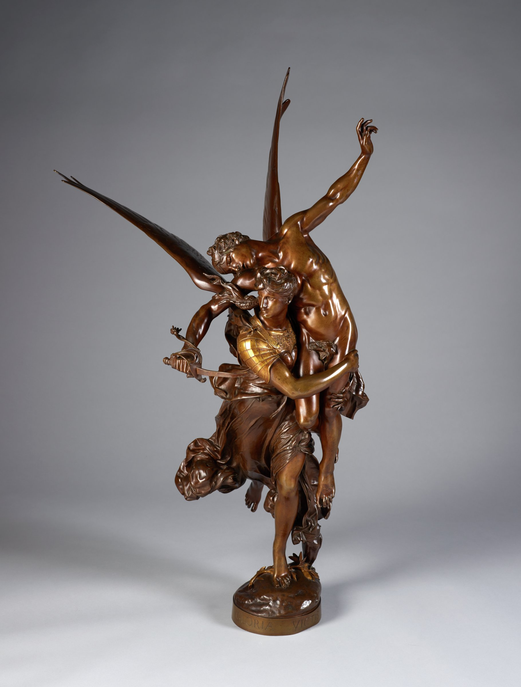 A winged woman figure wearing a long, flowing garment carries a nude male figure over her shoulder. The man stretches both arms out.