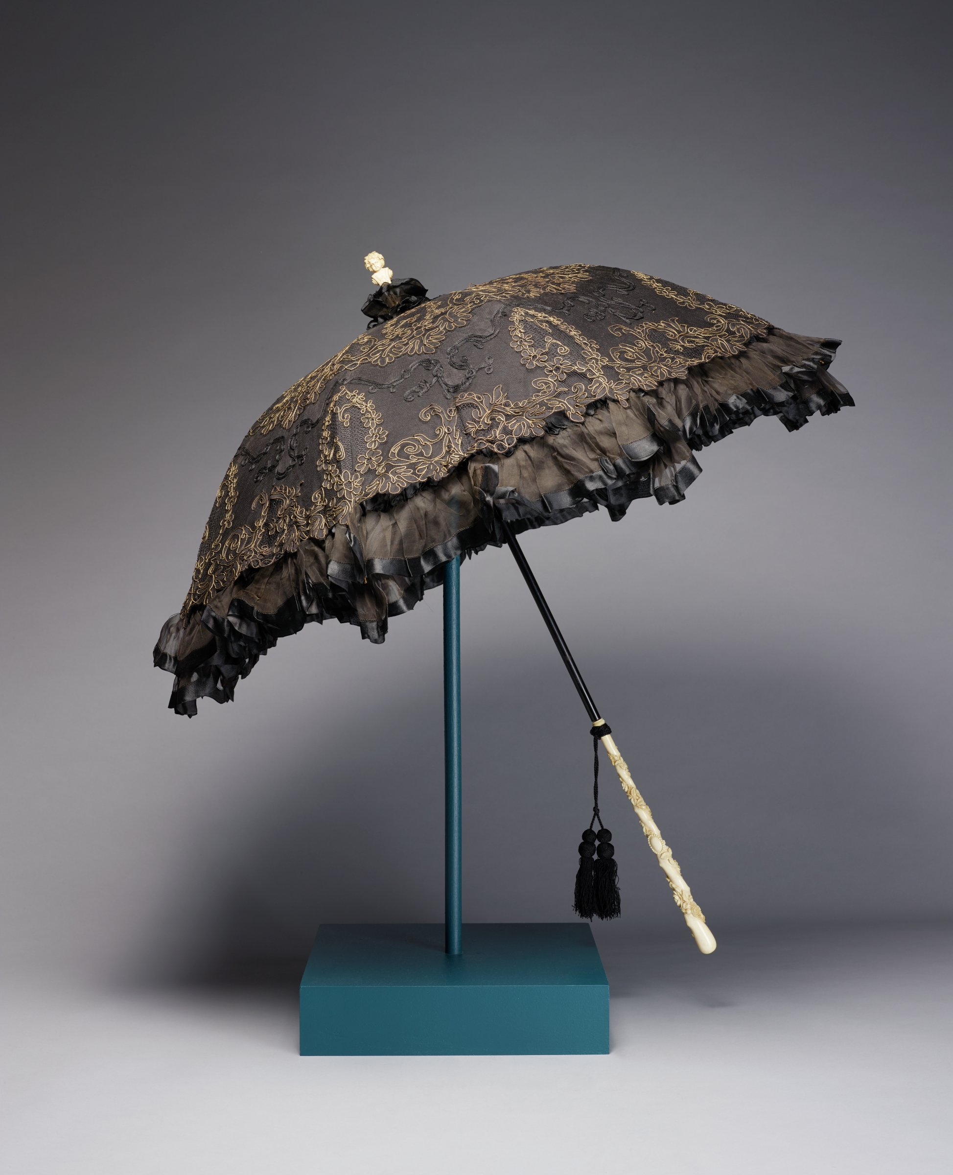 Ladies' parasol of black silk taffeta and lined with black silk, the canopy overlaid with black tulle, cut to reveal a subtle floral design with applied black cording and gold thread applied in a pattern of stylized leafy floral motifs, with ruffled edge with black satin banding and tuft of black silk at the top, the tapered handle/stick of ivory carved in relief with a floral garland that winds around the stick, the spike in the form of the bust of a bacchanalian figure likewise in carved ivory, with two tassels attached to the stick with black twine, the frame of black and gold tone metal.