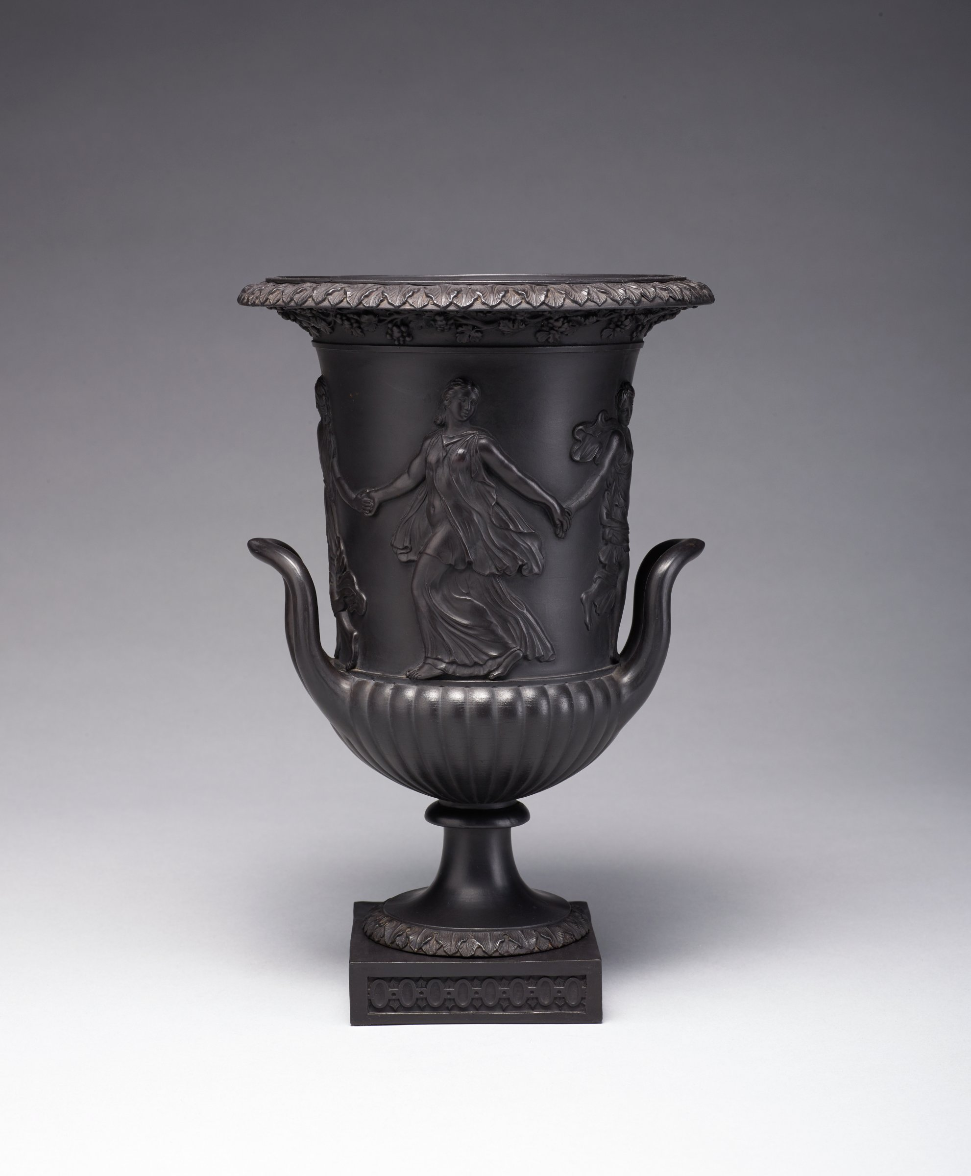 Tall campana urn-shaped vase of black basalt on a small square plinth edged in a molded diaper pattern, the lower body gadrooned, with two short loop handles, the main body with molded relief decoration of the Dancing Hours figures, nude and partially draped, with overlapping leaf motifs around the foot and lip, immediately under the lip is a frieze of grape and grape leaves.