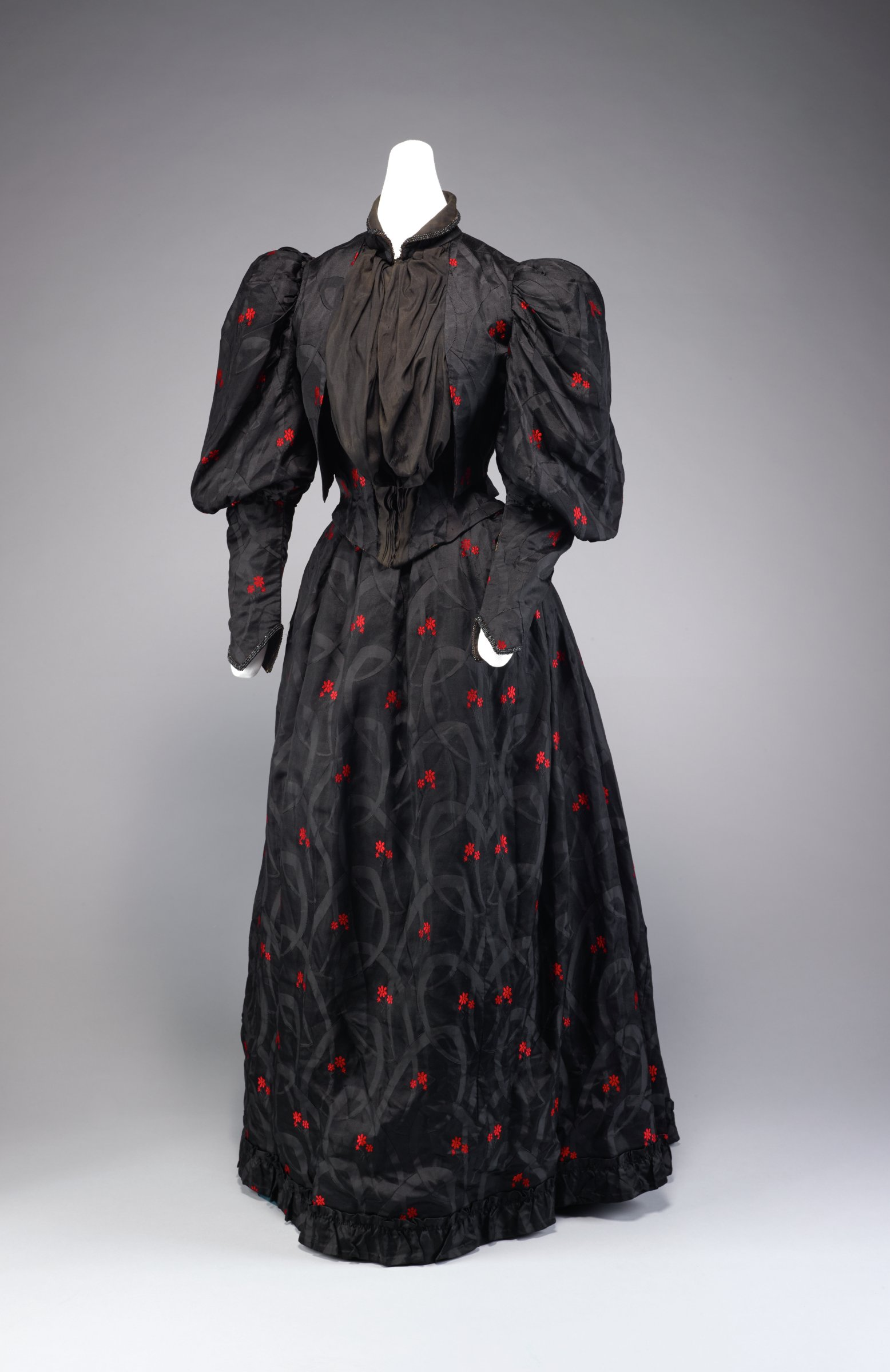 Two-piece black moiré silk dress embroidered with bright red flowers, comprised of bodice and skirt, the bodice with high, stiff, straight collar and loose inset blouse of plain black silk with nipped waist and back tie, with leg-of-mutton sleeves, the tulip bell skirt with ruffled hem, the back gathered at the waist and with a slight train.