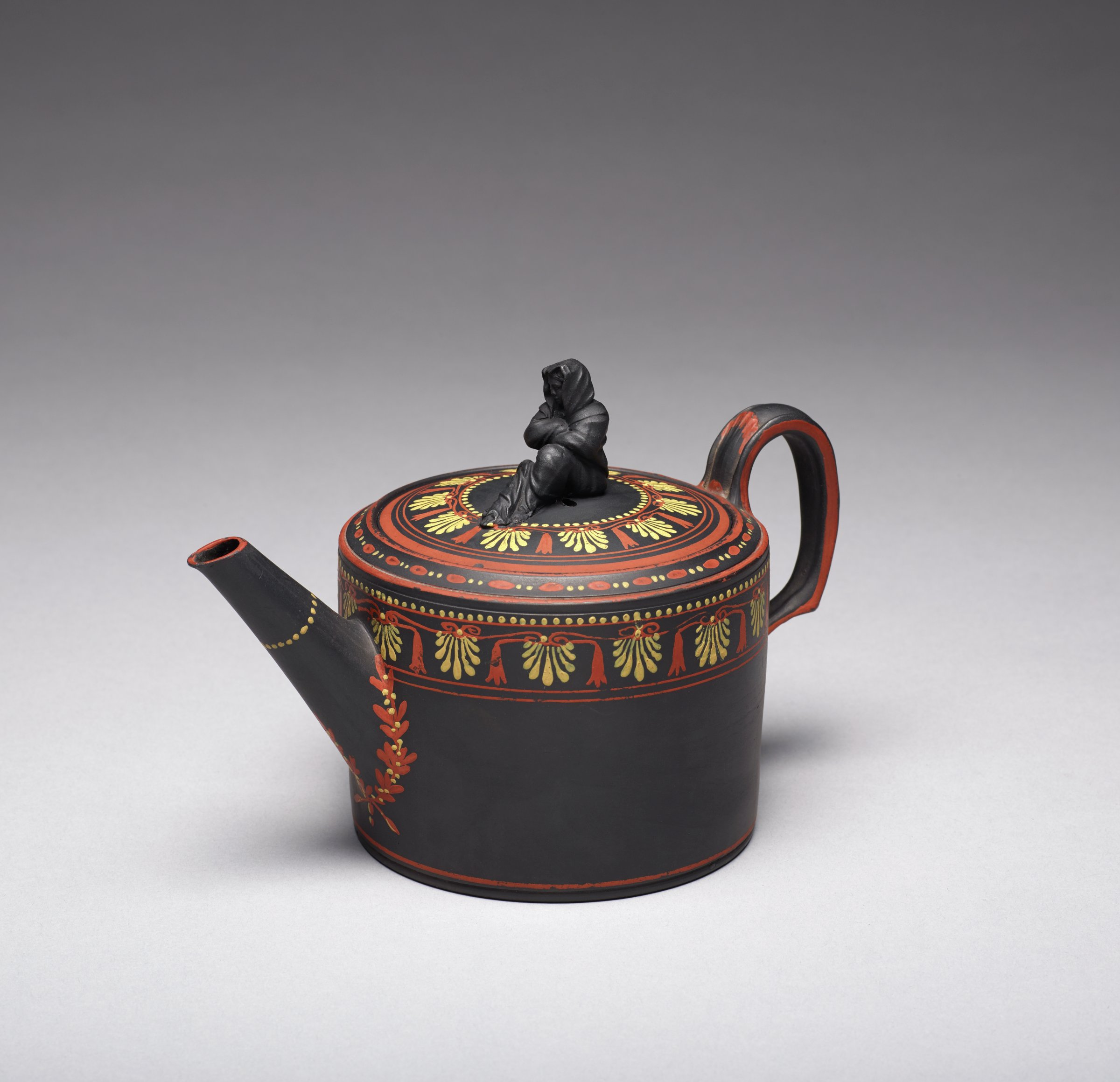 Covered teapot of black basalt with encaustic decoration, the body cylindrical with ear handle and straight spout, around the upper body and on the cover a band of honeysuckle and bell design in red and yellow with a wreath around the spout, the rest of the teapot edged in red, with Sybil or widow finial, the interior glazed and with pierced strainer.