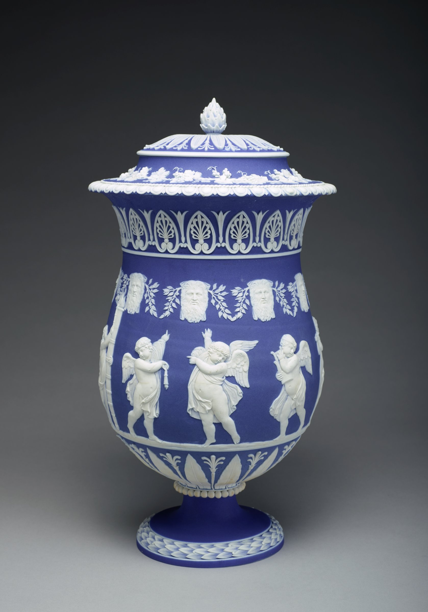 """Tall, footed vase with cover in a deep blue and white jasper dip, the edge of the foot is decorated in white relief with a band of overlapping leaves and berries delicately shaded to give the impression of translucency, the stem features a band of beading where it meets the body, the lower body is decorated in a stiff leaf / lotus pattern, the main body is decorated in the round with a group of cherubs, or """"geniuses"""" each carrying symbolic objects or playing musical instruments; above the figures is a border of nine bearded men interspersed with laurel branches and above this a border of anthemion motifs, the upper edge of the vase is decorated with an egg-and-dart pattern below a narrow band of ropework, the neck features a band of of grape vines and leaves with bunches of grapes, the conforming domed cover has a similar stiff leaf / lotus pattern and pine cone finial."""