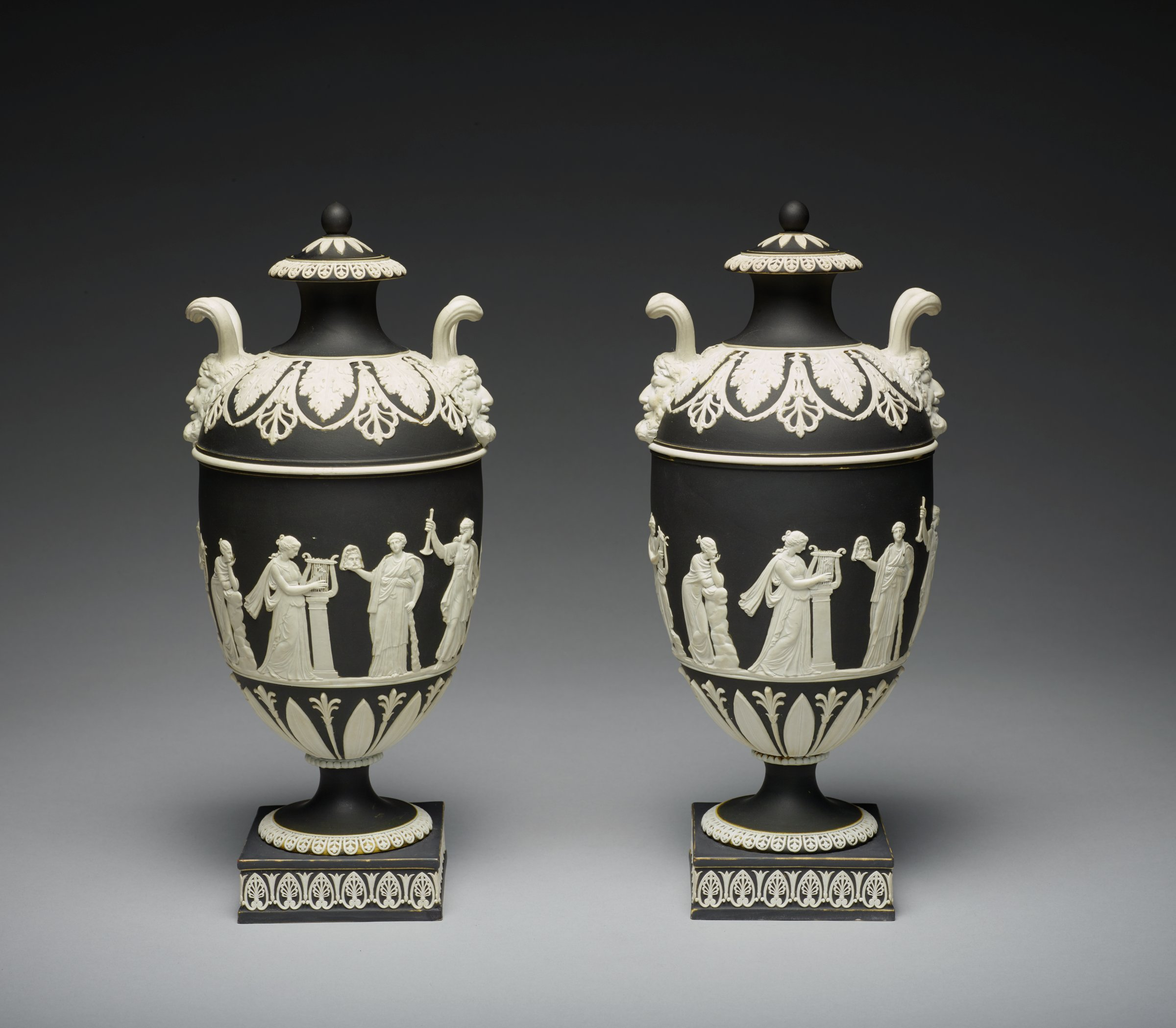 Pair of white jasper urns with black jasper dip and white relief decoration, each on a square plinth with anthemion motifs around, round foot with floral motifs and beading on the stem, the lower body with stiff leaf and lotus motifs and the main body with scene of Apollo and the Muses (one vase does not have the Apollo figure) and above this a band of white, the shoulder decorated with acanthus leaves and leafy anthemion motifs, the terminals of the handles comprised of satyr masks, whose fluted horns extend up and connect to form an angular loop handle, with plain neck and flared lip with like floral band, the small conforming cover with stiff leaf elements and ball finial, the interiors white and with sump covers.