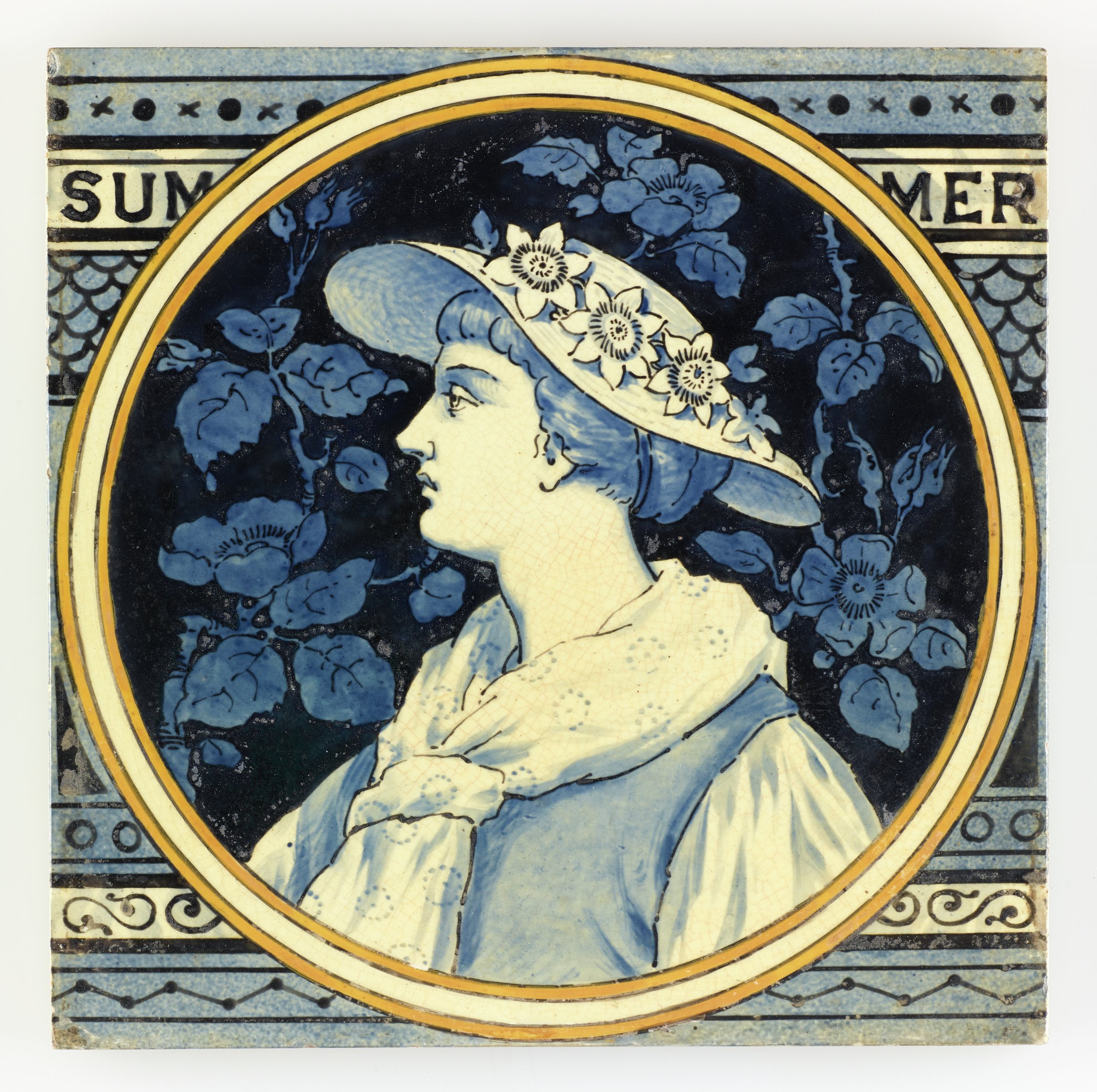 Large, square earthenware tile partially printed and hand-painted with a circular reserve outlined by a white band within two yellow bands containing in white with blue highlights the portrait of a young woman to left wearing a summer blouse and vest with a loose scarf and a straw cap with a band of flowers, the ground with a blue on blue design of floral vines, the larger ground of the tile contains in various shades of blue a pattern of decorative, horizontal bands with from the top a band of small x's and solid dots; the name of the season SUM MER; a fish scale pattern; a band of open dots; a band of scrolling motifs; and a band featuring a zigzag design, the reverse with horizontal bars in relief to aid adhesion when setting the tile.