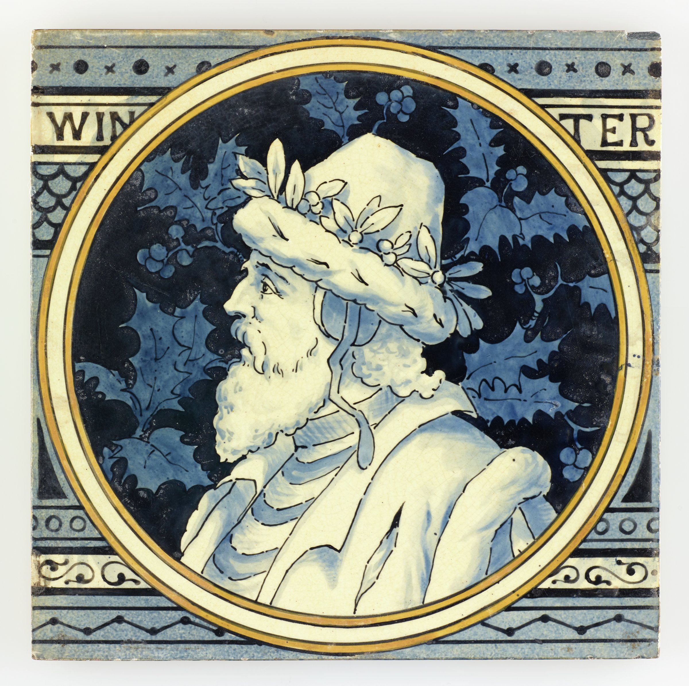Large, square earthenware tile partially printed and hand-painted with a circular reserve outlined by a white band within two yellow bands containing in white with blue highlights the portrait of an older, bearded man to left wearing a fur coat and ermine cap with ear muffs, the cap has a band of holly, the ground with a blue on blue design of holly sprigs, the larger ground of the tile contains in various shades of blue a pattern of decorative, horizontal bands with from the top a band of small x's and solid dots; the name of the season WIN TER; a fish scale pattern; a band of open dots; a band of scrolling motifs; and a band featuring a zigzag design, the reverse with horizontal bars in relief to aid adhesion when setting the tile.