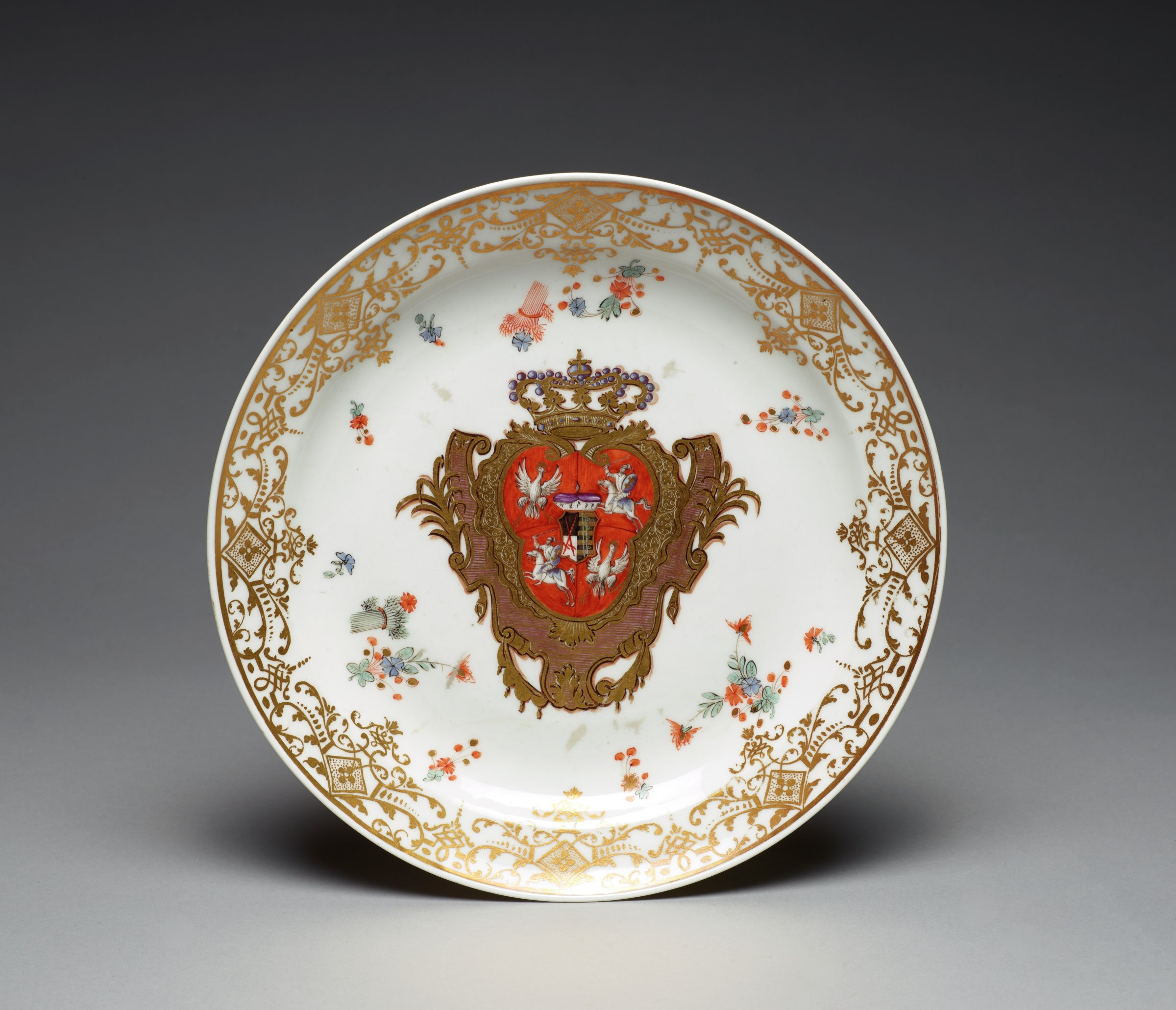 Round dinner plate of white porcelain decorated with elaborate gilt scrolls around the rim and with scattered flowers and sheafs of wheat reminiscent of the Kakiemon style in the well, in the center decorated with the quartered Arms of Saxony and Poland centered with the small crest of the Saxon Electorate showing crossed swords, within a crowned escutcheon.