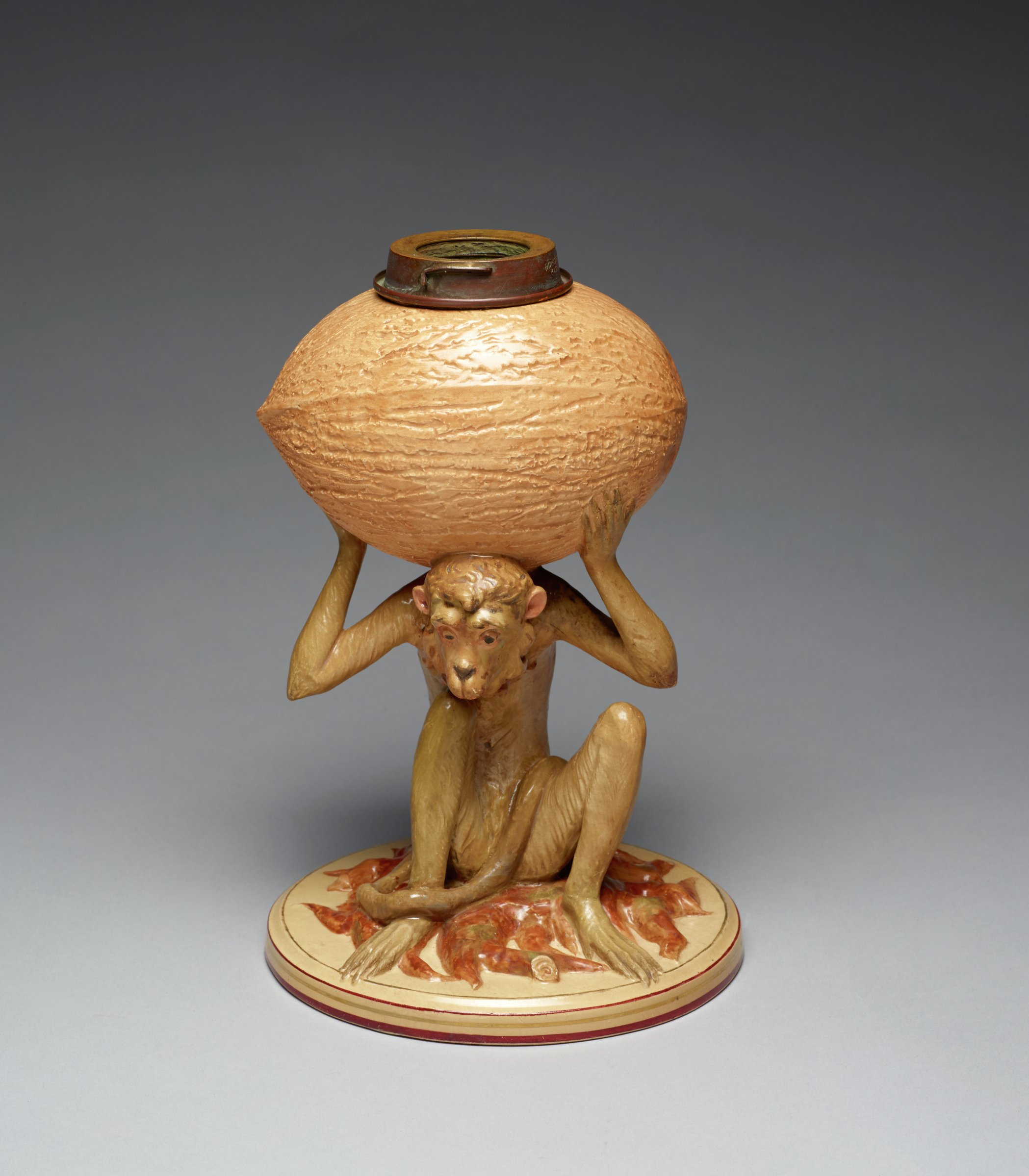 Lamp base of Majolica in the form of a brown monkey seated on a round base covered with molded leaves and twigs in shades of red, holding a large nut on his head supported by both arms, the original oil burner, chimney and shade of the lamp are now missing.