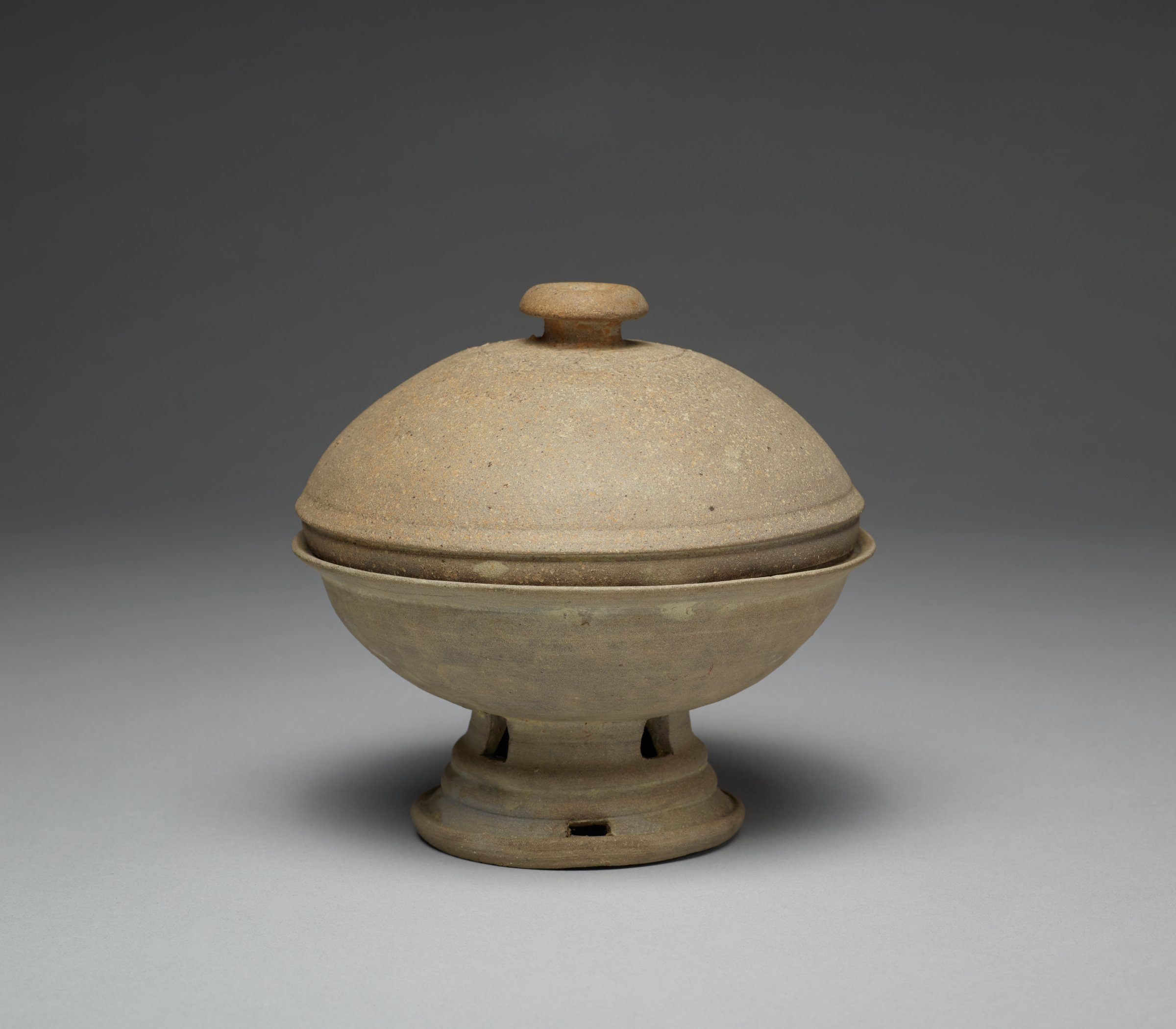 Perforated foot for base of bowl, cover decorated with lightly incised floral design around knob