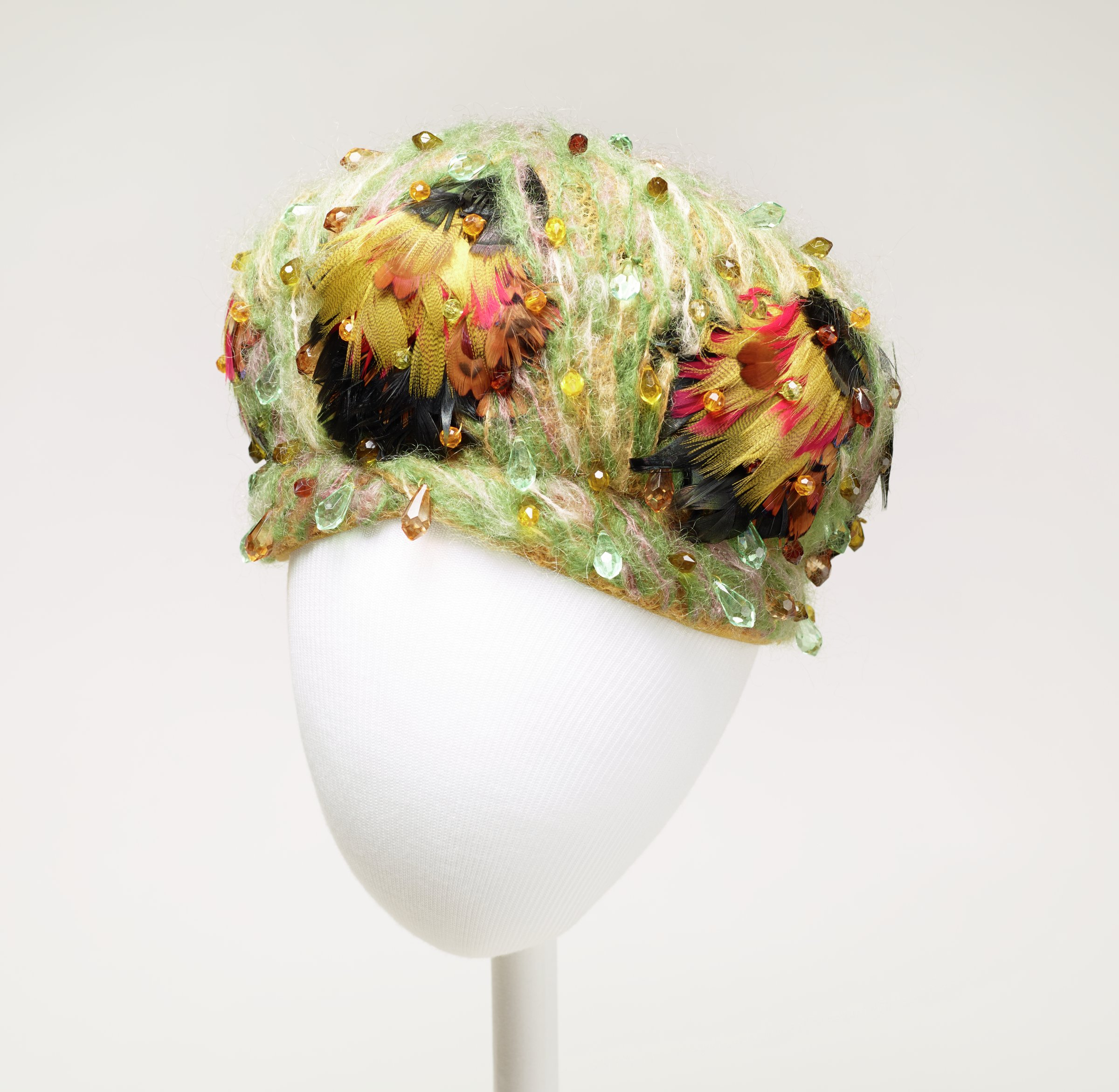 """Ladies' cap-like hat of green and beige wool mohair on a tulle foundation and decorated with colorful feathers in red, yellow and black and cut """"crystal"""" multi-colored beads."""