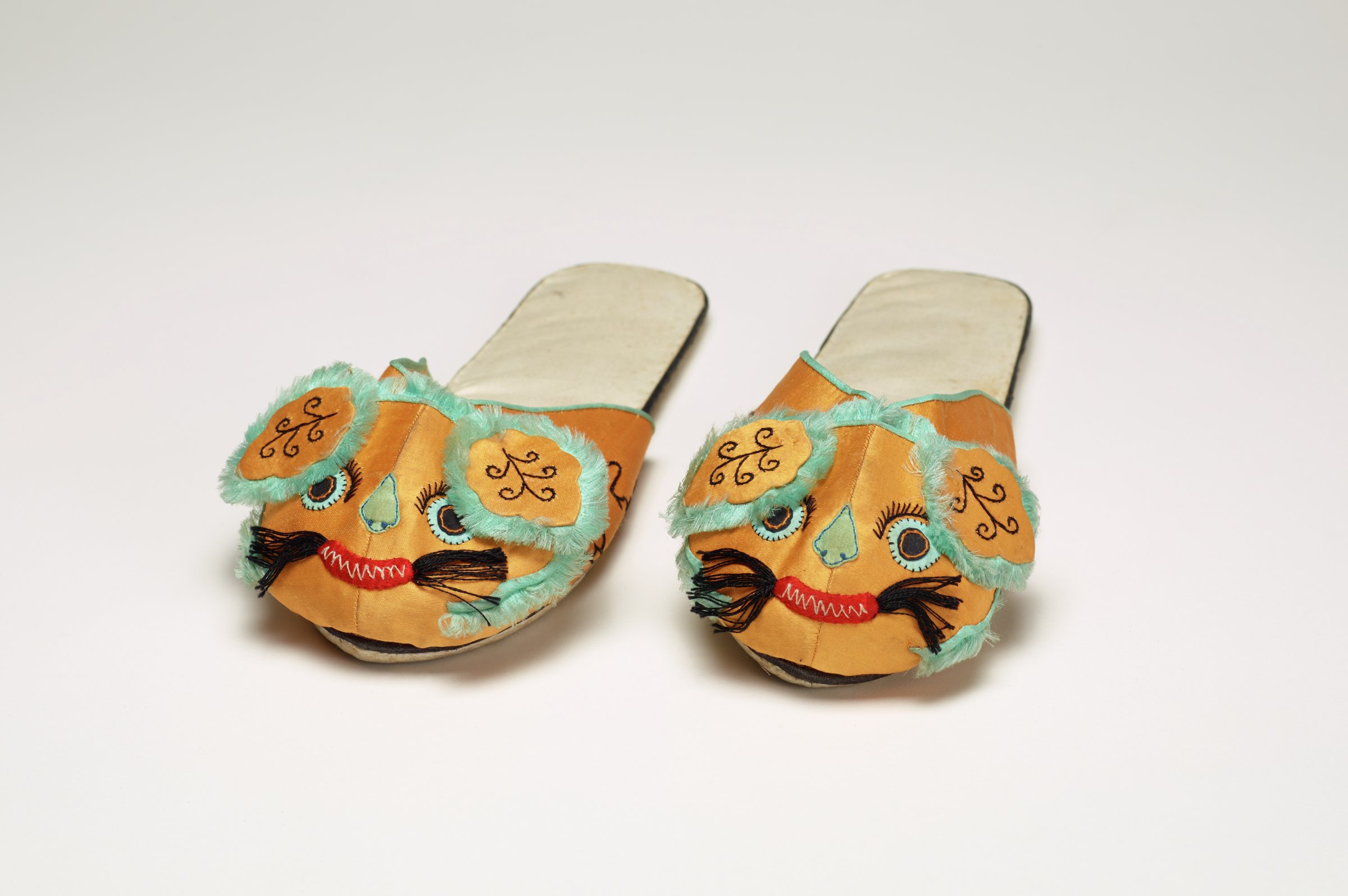 Yellow silk slip-on slippers with lion faces done in embroidery and appliqué for the toes.