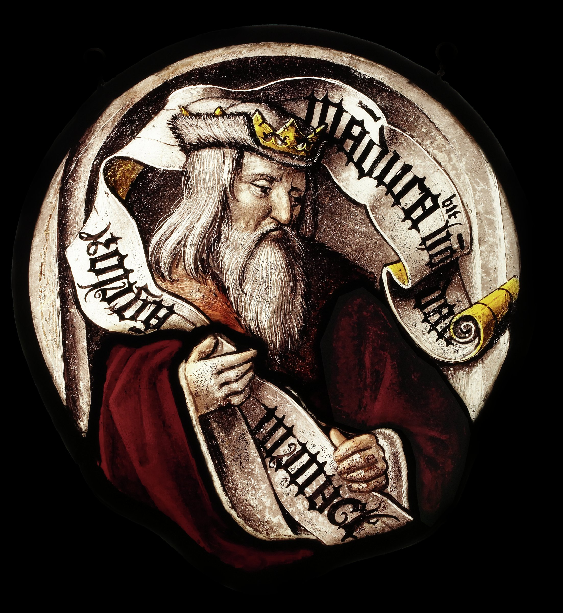 A bust-length image of King David with long white hair and beard wearing a crown and holding an inscribed banderole.