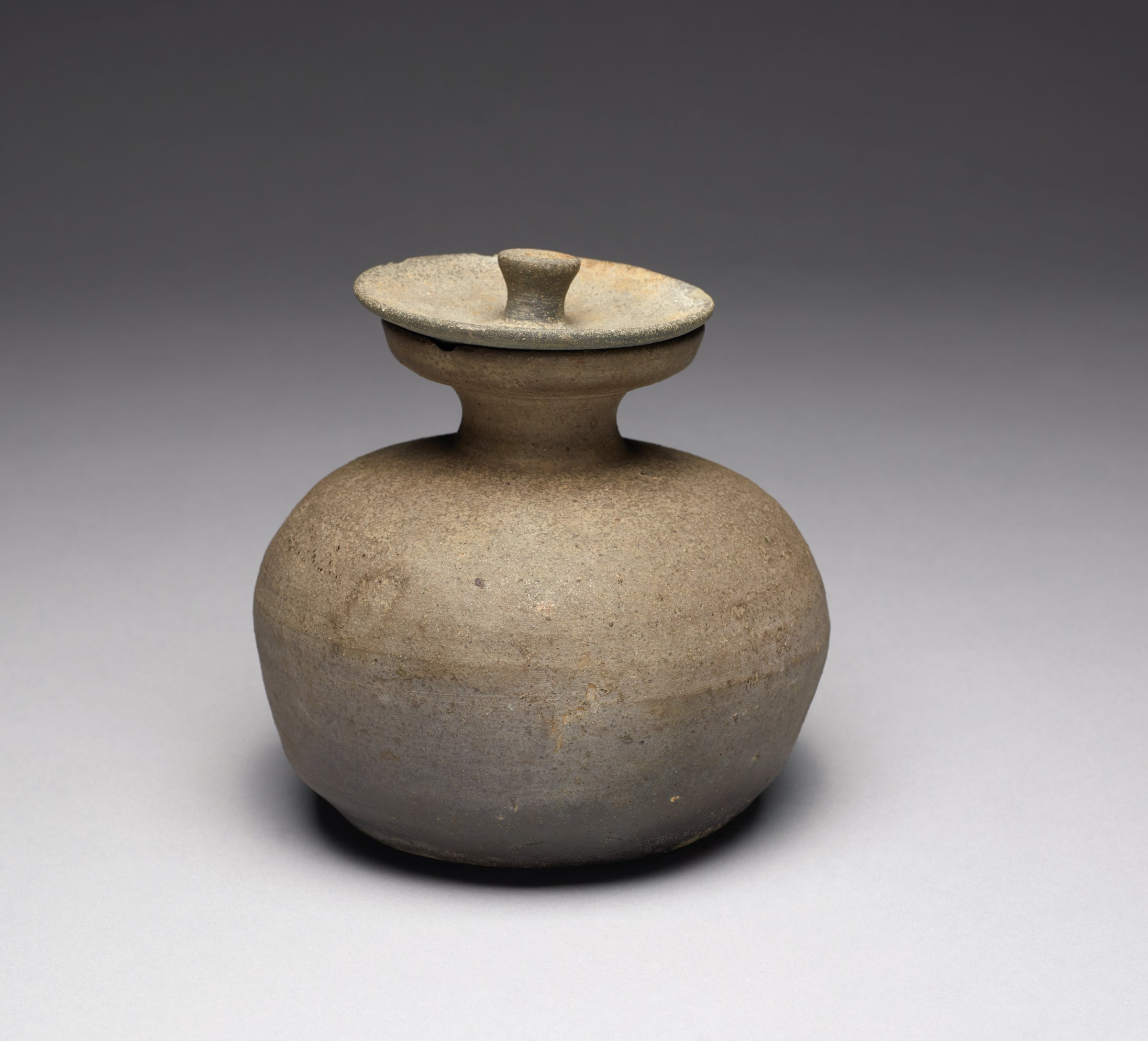 Globular form jar with slight traces of ash glaze. Cover has inverted tang.