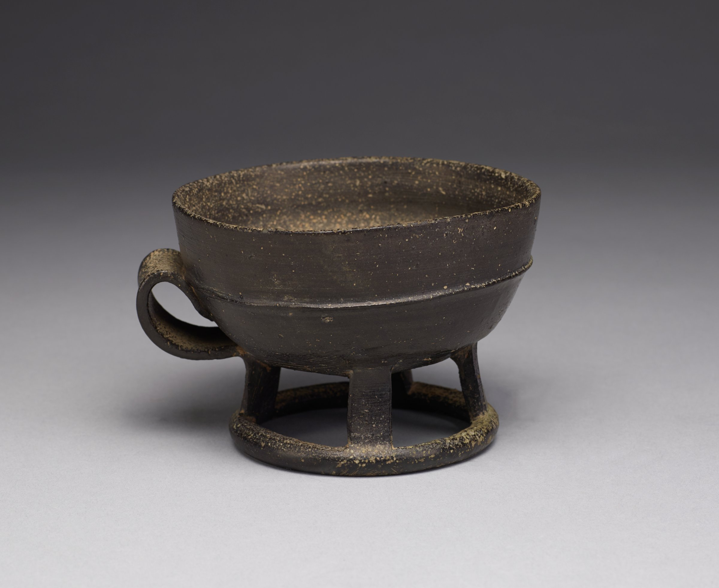 Cup is footed with a handle. Outer part of cup and inner rim covered with deep, lustrous black glaze thinly coated and pitted.Thinkly potted no visible repairs.