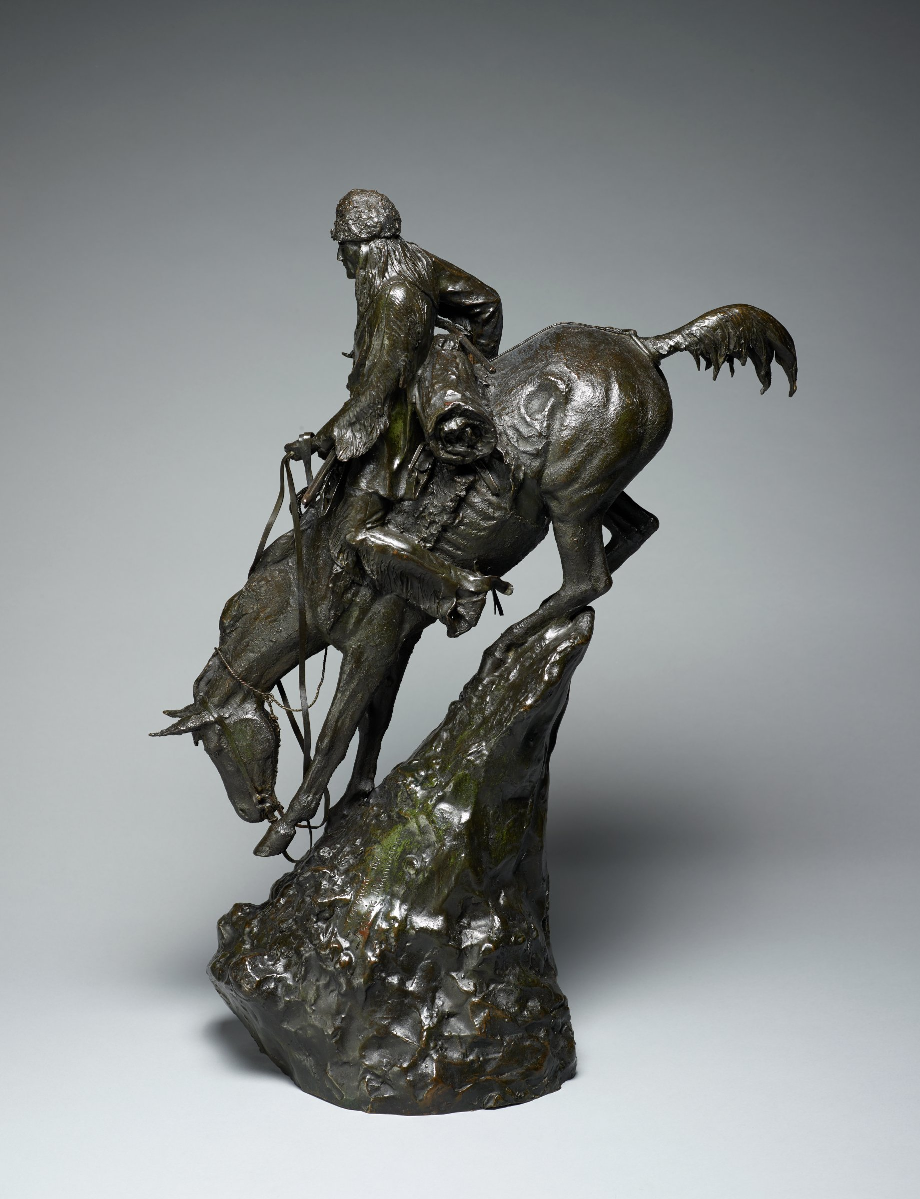 A mountain man, probably a trapper, leads his horse down a steep incline. Across his saddle he balances his rifle, while he grips the back of his saddle with his right hand. His long straight hair falls from beneath a woolen hat.