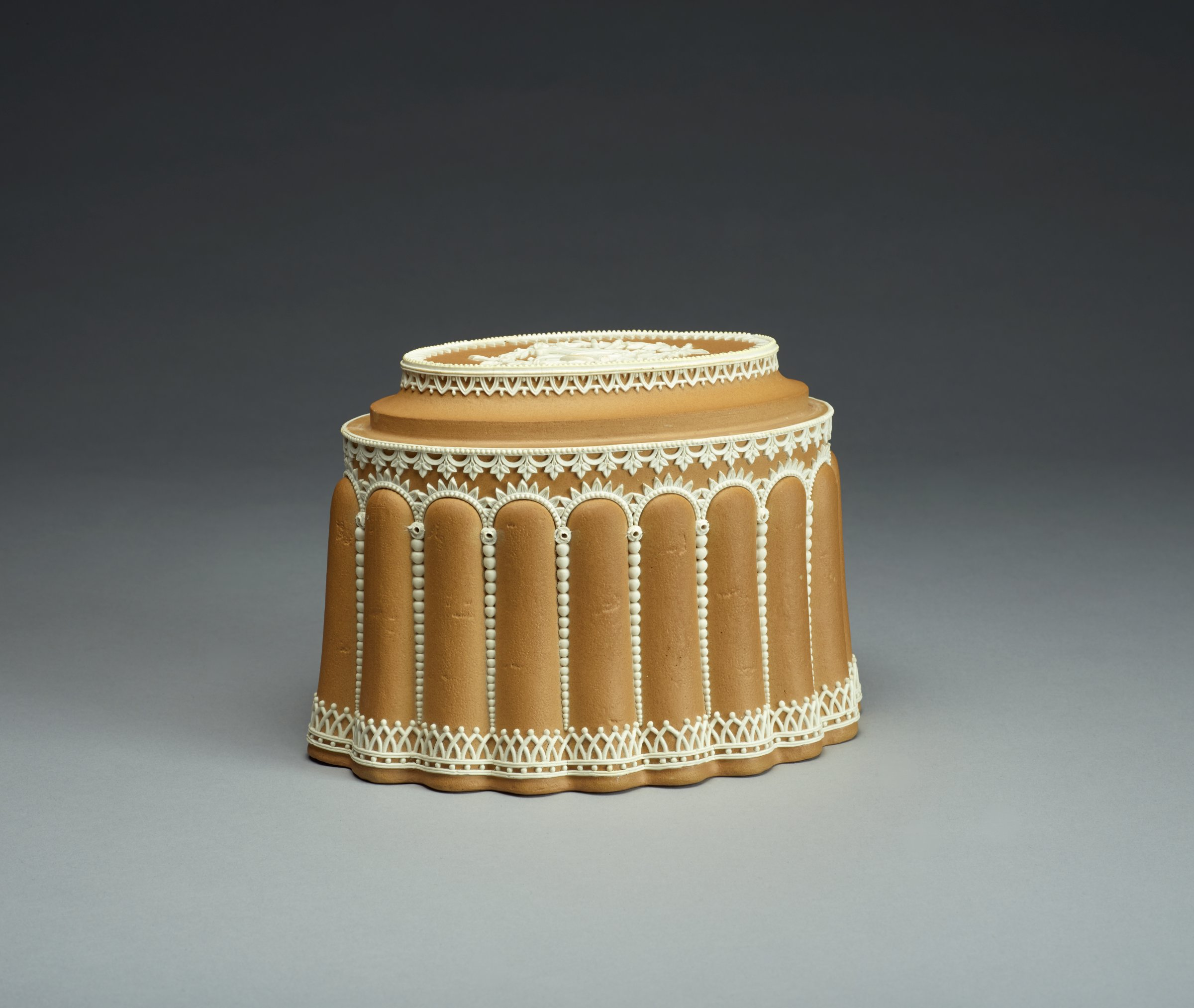 Caneware conceit (shape 419 in Shape Book) in the form of an oval, tiered cake with sides made of lady fingers and white stoneware applied relief that simulates icing in a design of beading within arched and interlaced borders, on the top an intertwined laurel wreath with musical trophies inside, with a solid flat base with a single large firing hole.