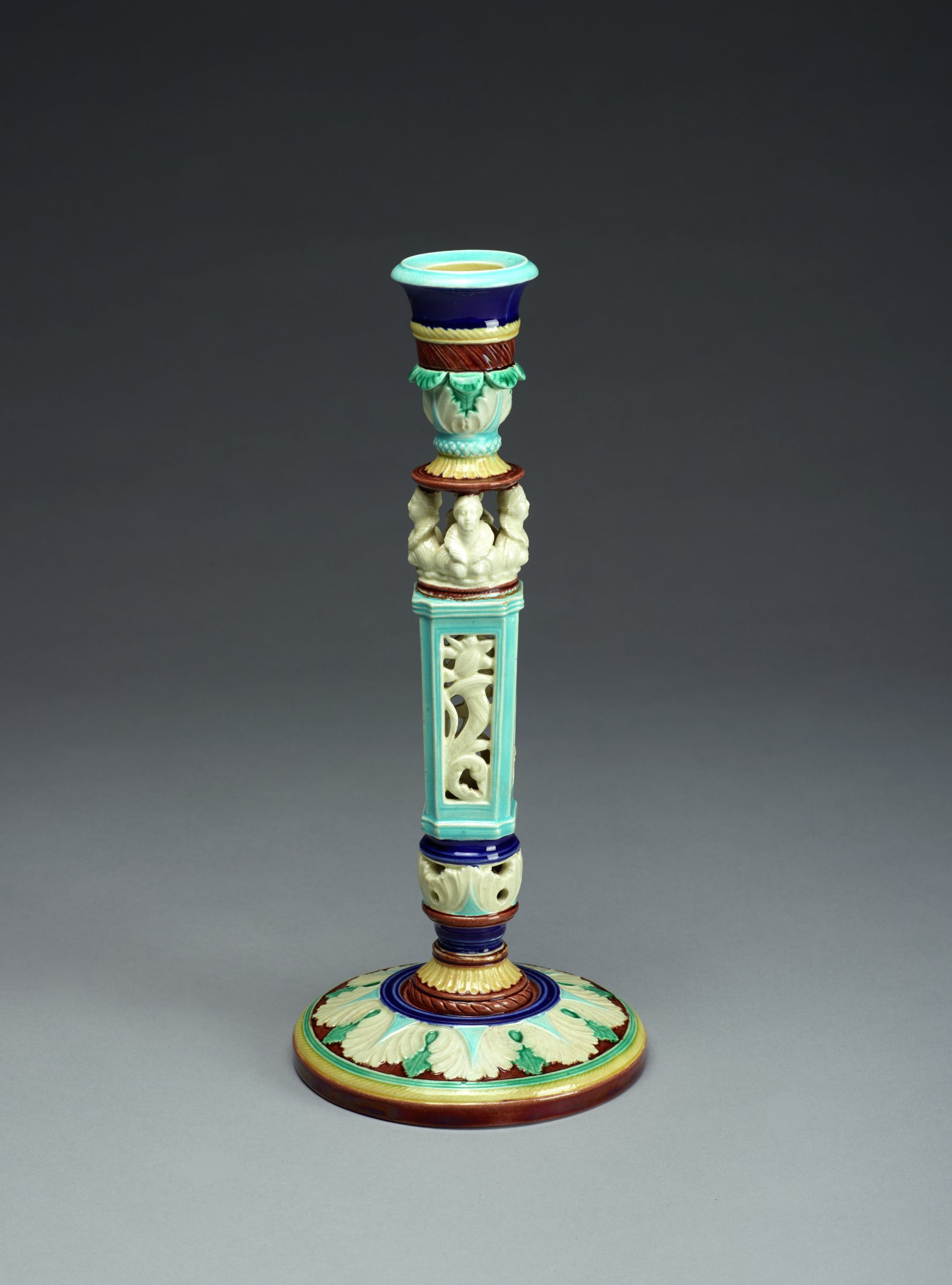 Tall, narrow candlestick in the 16th century Renaissance style of colorful Majolica glazed in bright shades of green, blue, yellow, brown and white, of columnar form with round foot decorated with stylized acanthus leaves in low relief, the angular stem pierced with figures and scrolling floral elements below four female busts that support the leafy bobeche, the nozzle in the shape of an urn.