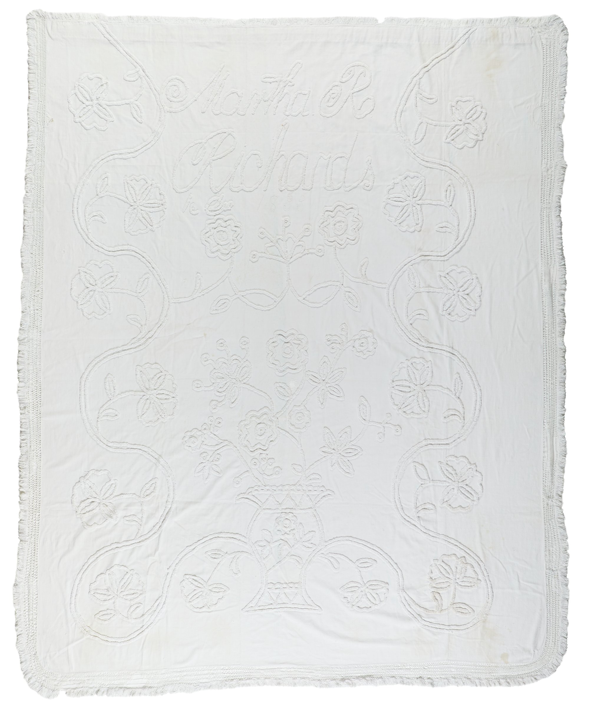 """Large unbleached plain-weave white cotton bedspread or coverlet made up of three vertically oriented panels stitched together and decorated with white candlewick embroidered floral motifs, at the top in large letters the signature and date """" Martha R. Richards / 1833,"""" below the signature an urn with flowers and vines at bottom center with flowers filling the central portion of the coverlet and vines snaking along the left and right edges with flowers emanating from them, the two long sides and lower edge finished with a knotted border and fringe of unbleached cotton, the top edge is finished with a border of cotton fringing."""