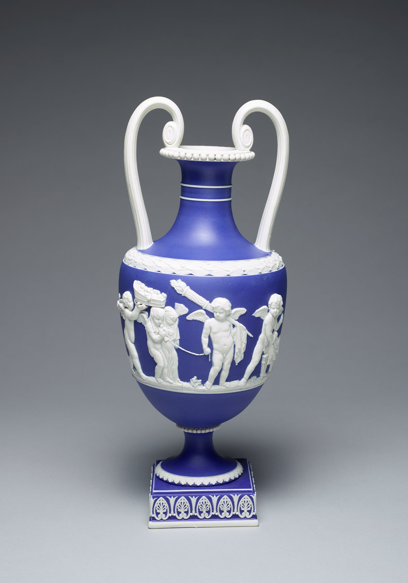 Tall vase of deep blue jasper dip with white jasper relief decoration, resting on square plinth decorated with white anthemion motifs, the round foot with overlapping acanthus leaves and beading at the joint, the main body with applied white relief of on one side the Marriage of Cupid and Psyche, the other side left blank, the shoulder with a wide band of overlapping laurel leaves, with two scrolled handles and beading at the lip, the neck with a pair of thin white parallel bands.