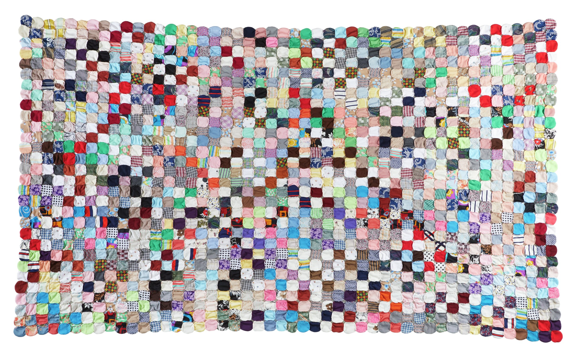 Large, rectangular yo-yo quilt or coverlet made from round pieces of cotton-polyester blend fabrics in a wide variety of patterns and colors, including gingham, houndstooth, stripes, plaids, floral and geometric prints, polka dots, and plain colors, that have long stitches along their turned-under outer edges, which are pulled to form small rosettes or discs, each hand sewn side by side with red thread into rows to form the quilt, no batting and no backing.