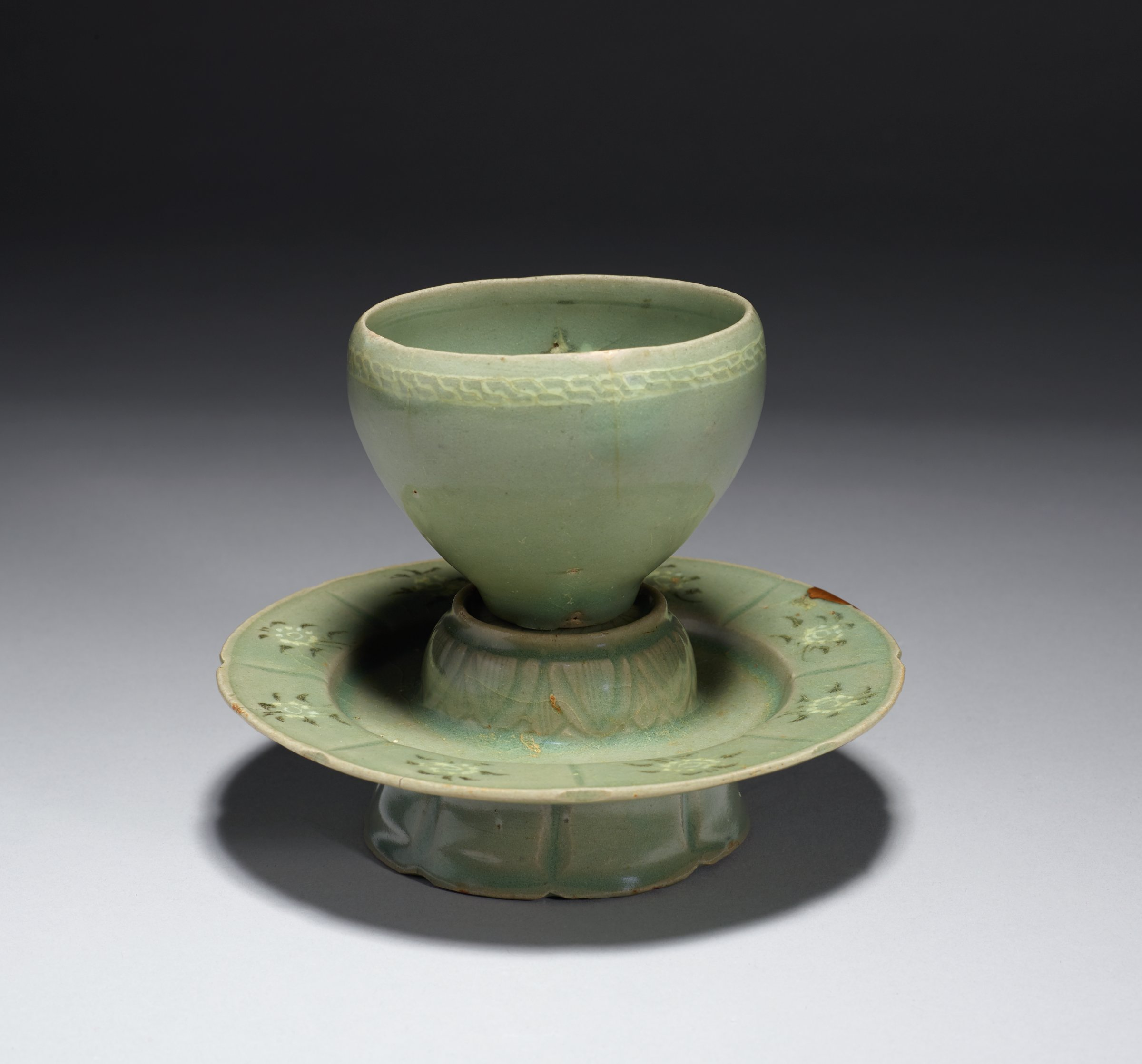 Cup with Interior Peony Motif and Exterior Meandering Key Border and Saucer with Lotus and Peony Motifs. Pressed glaze on outer lip during firing. gold lacquer repair on saucer lip