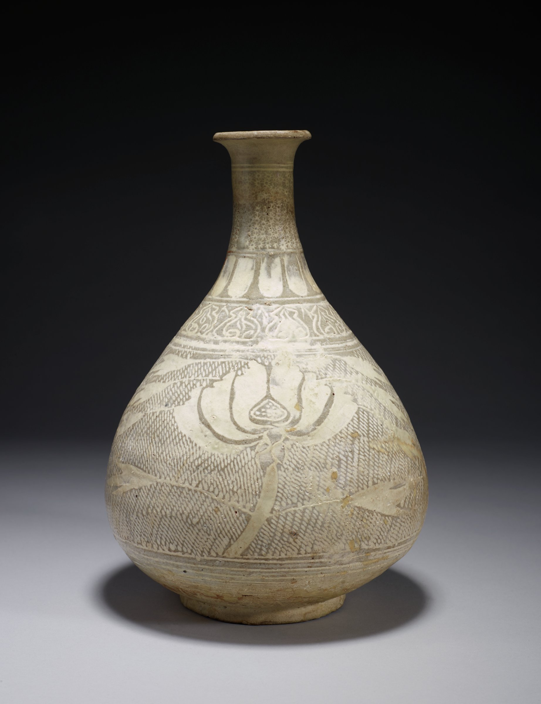 Pear-Shaped Bottle with Long Neck and Peony and Petal Motif. Star/Jasmine(?) flowers on neck under clouded glaze. Deeply carved leaf ring. Reddish clay underneath.