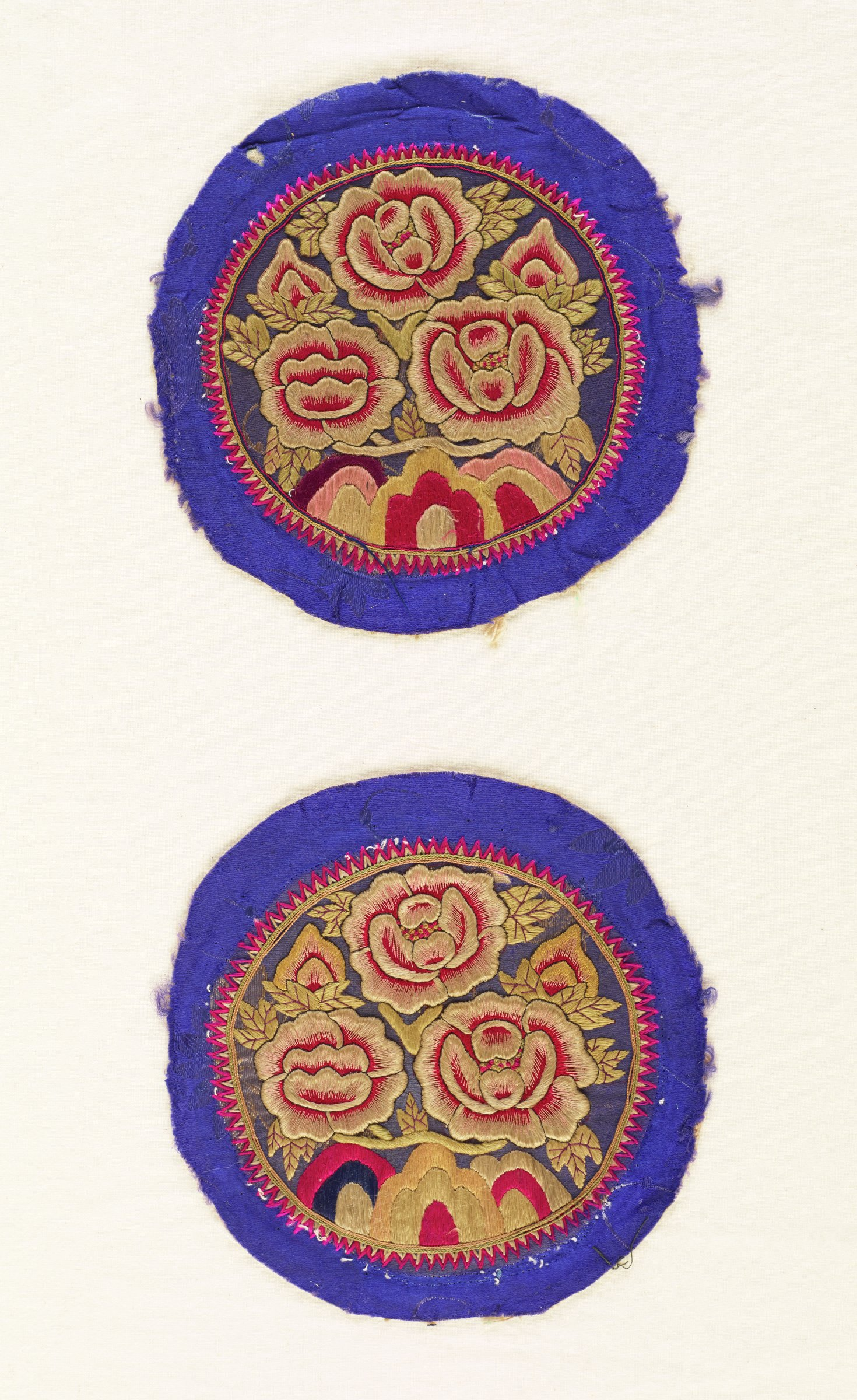Pair of round pillow ends with embroidered floral designs on royal blue background
