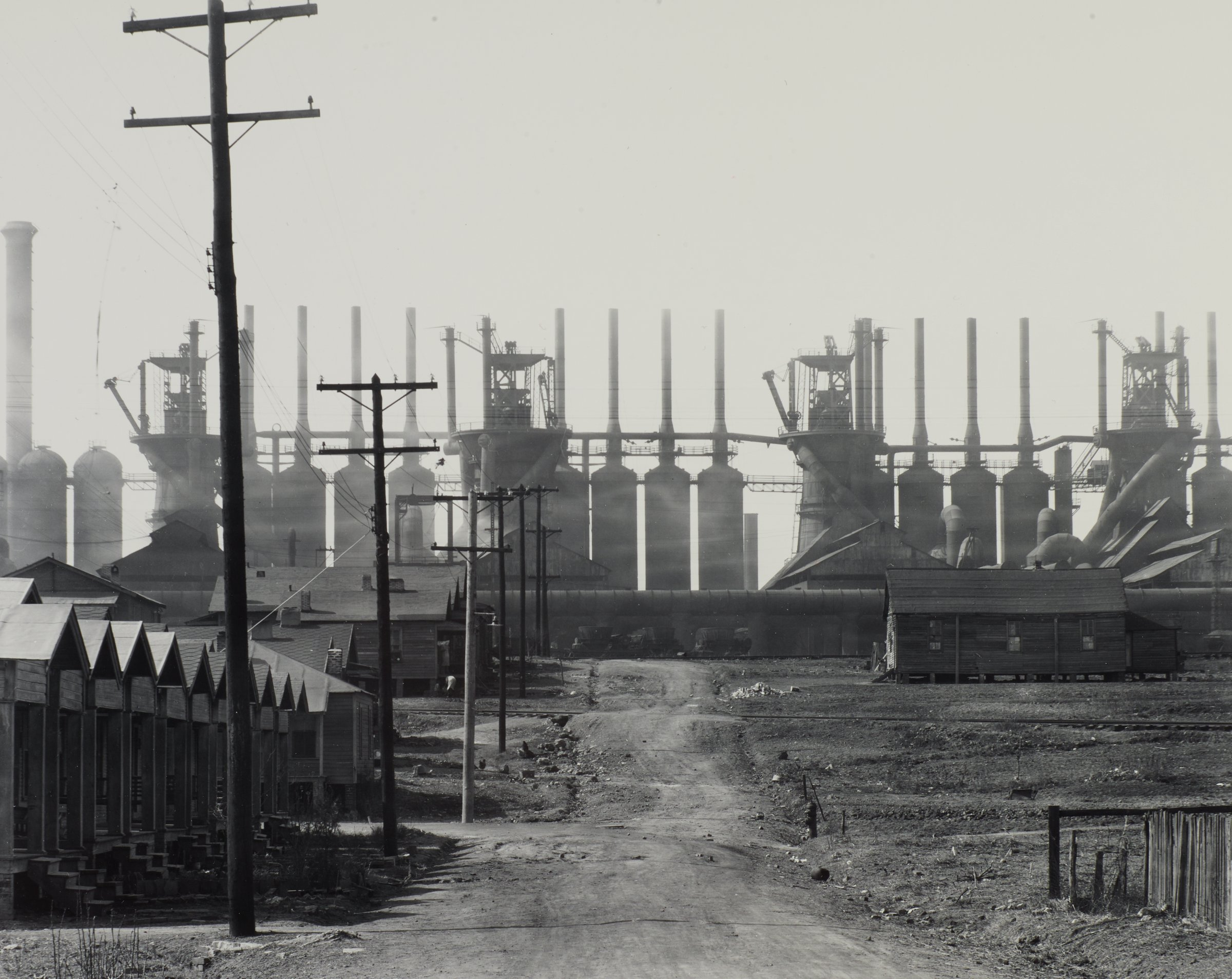 A black and white photographs featuring a dirt road leading up to a Steel mill in the background. The steel mill is the Ensley Works steel plant in Birmingham, Alabama. To the left of the dirt road is single story smaller houses, with some larger structures to the end of the road, and one on the right side of the road as well. Power poles also line the road on the left side, leading up to the steel plant. The furnaces of the plant are wider towards the base with much thinner chimneys on the top.