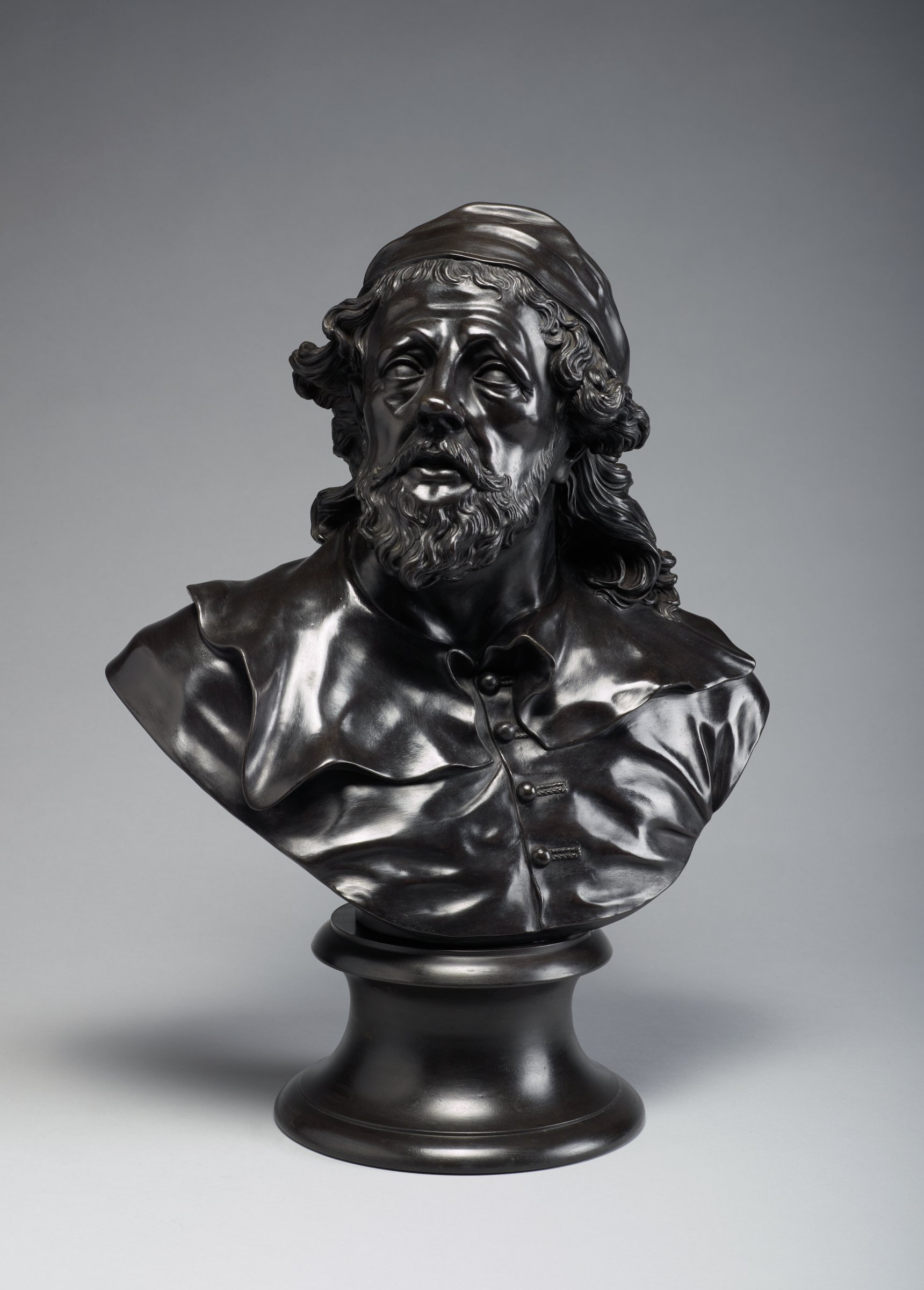 Large library bust of the English architect Inigo Jones in black basalt, bearded and with long hair, his head turned slightly left and his lips parted, with skull cap and buttoned waistcoat with wide collar, on round pedestal.