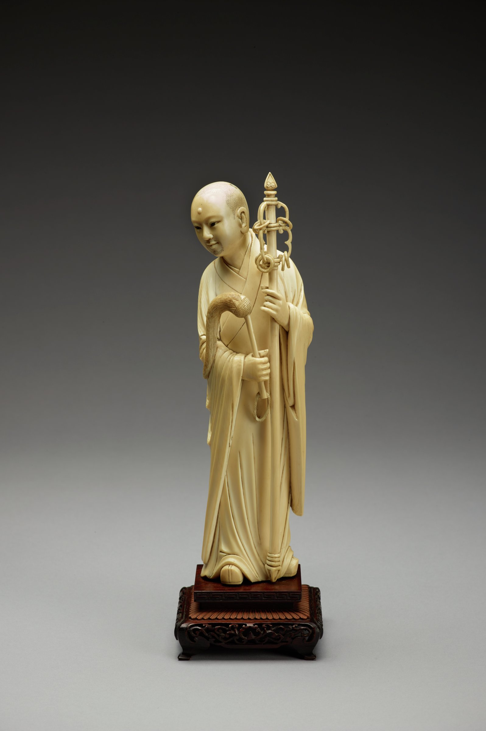 Standing shaven headed youthful monk with kkhakara carrying staff and flywisk on square wooden base