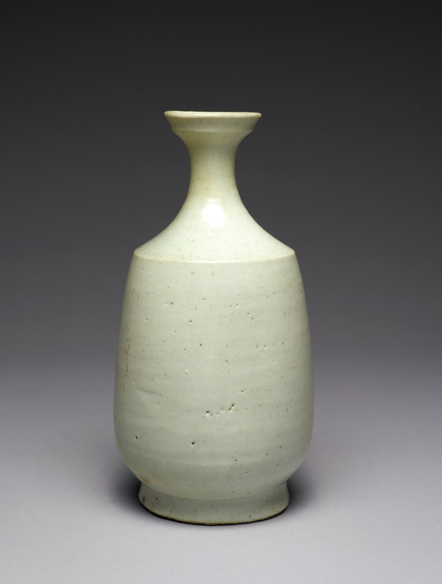 Slightly conical form with angular shoulder top with a dish mouth, supported on splayed footring; free of decoration, covered in whitish glaze; gritty footring from firing. Nice weight. Five glaze deposit spotting around shoulder.