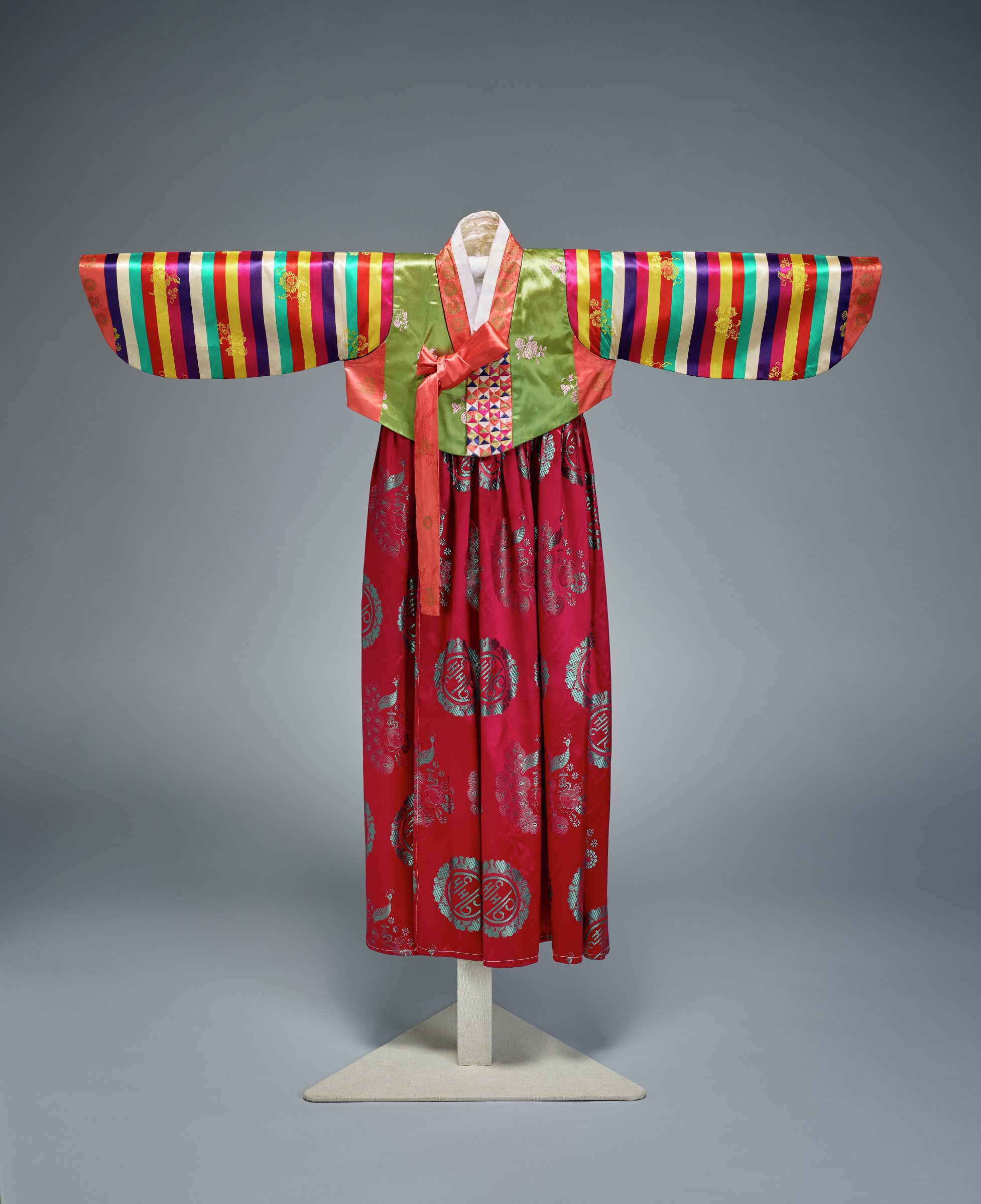 Traditional jacket and skirt for a Korean young lady. Jacket has embroidered flowers and birds with multi-colored stripes of cloth on sleeves. Skirt is solid dark grape purple with embroidered Chinese characters for happiness and images of peacocks.