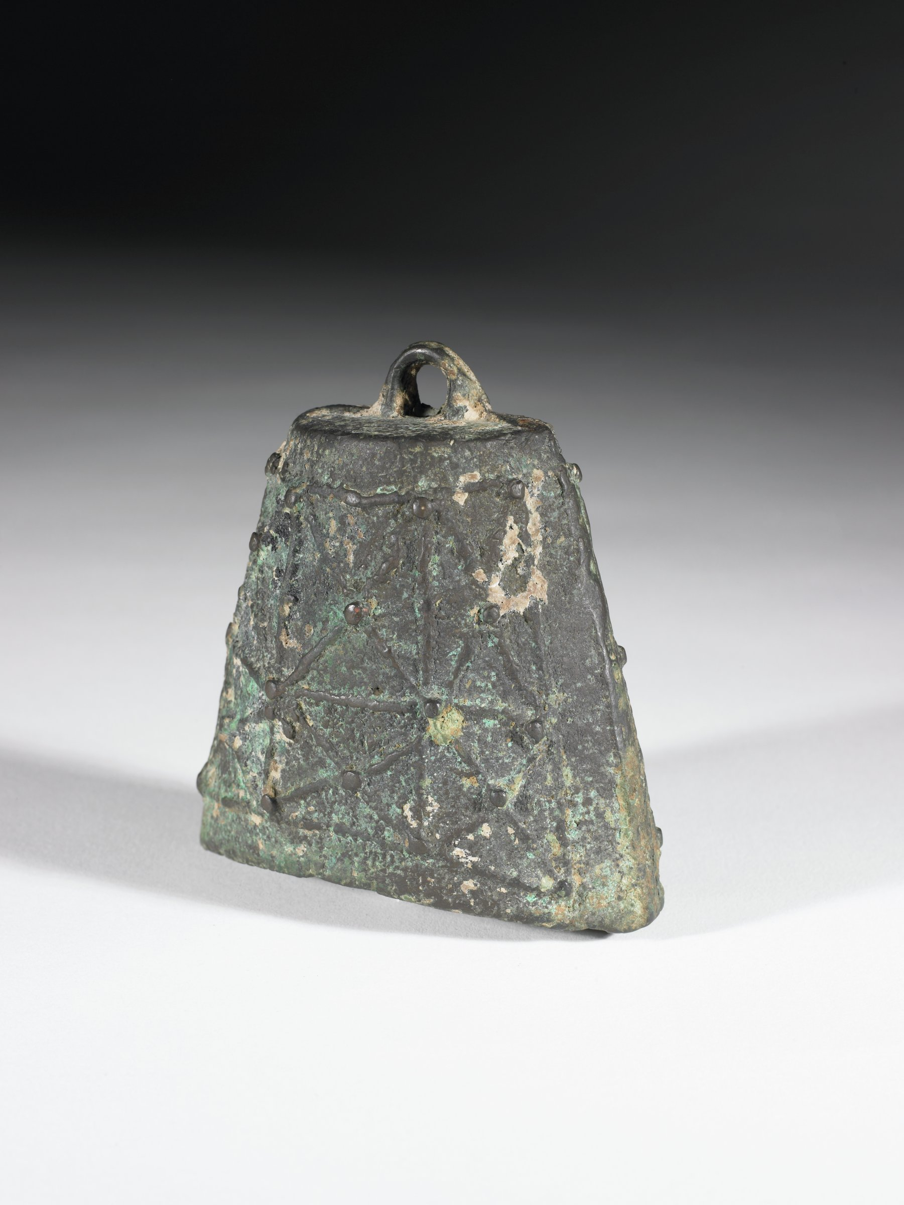 """Flattened trapezoidal bell with netting like surface motif composed or raised rectangles filled with """"x"""" that have a small boss at the intersecting lines. Hole at top for loop for clapper. dented on one side."""