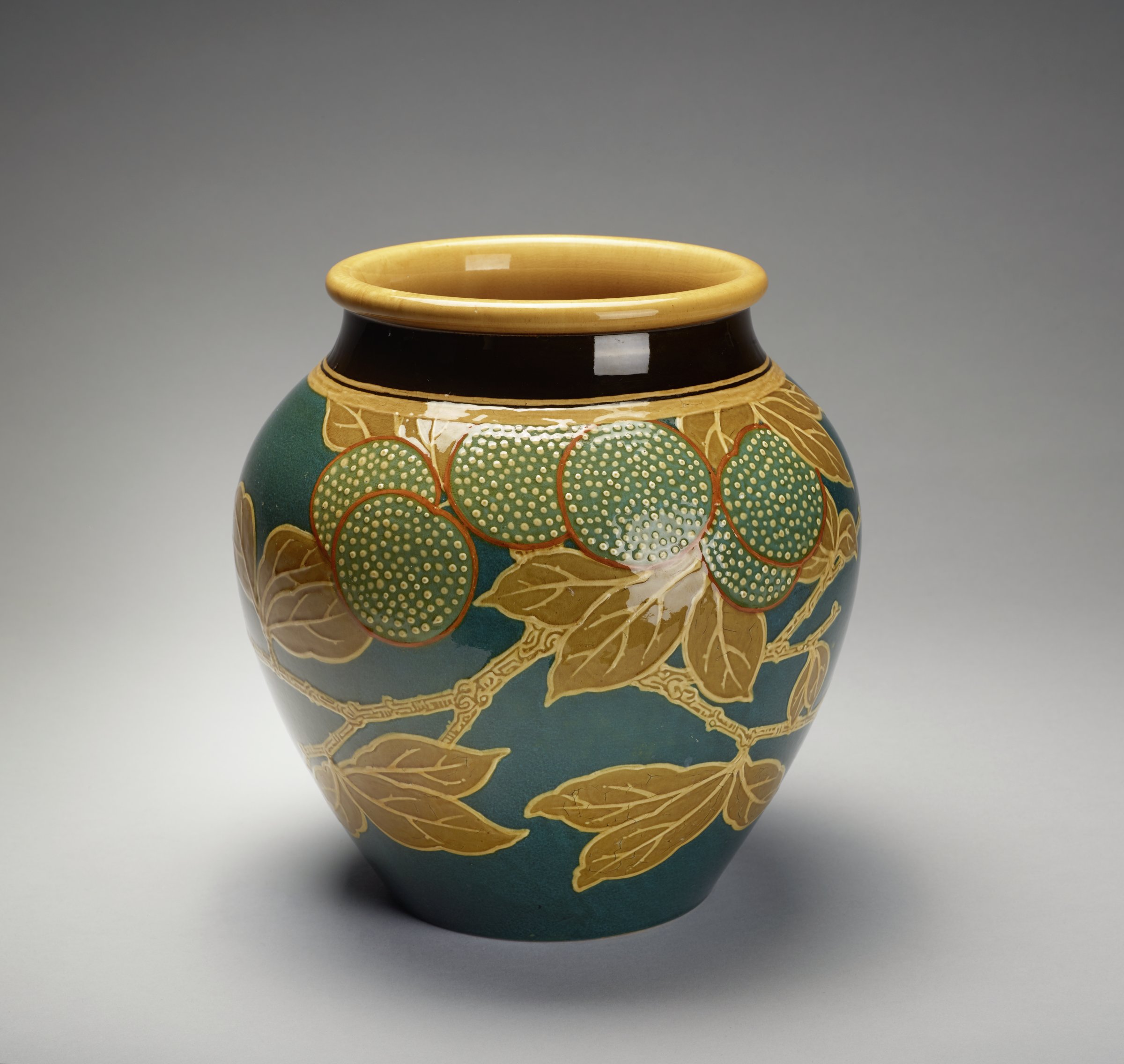 Large squat Marsden's Art Ware vase of glazed and slip-decorated earthenware, of baluster shape with rolled lip, the body interior and underside covered with a beige glaze, the main exterior body covered with a teal-blue glaze and decorated in a design of leafy branches in brown and beige slip and clusters of oranges in a light teal slip with beige dots indicating a typical orange-peel pattern, the neck with a wide brown band above narrow beige bands.