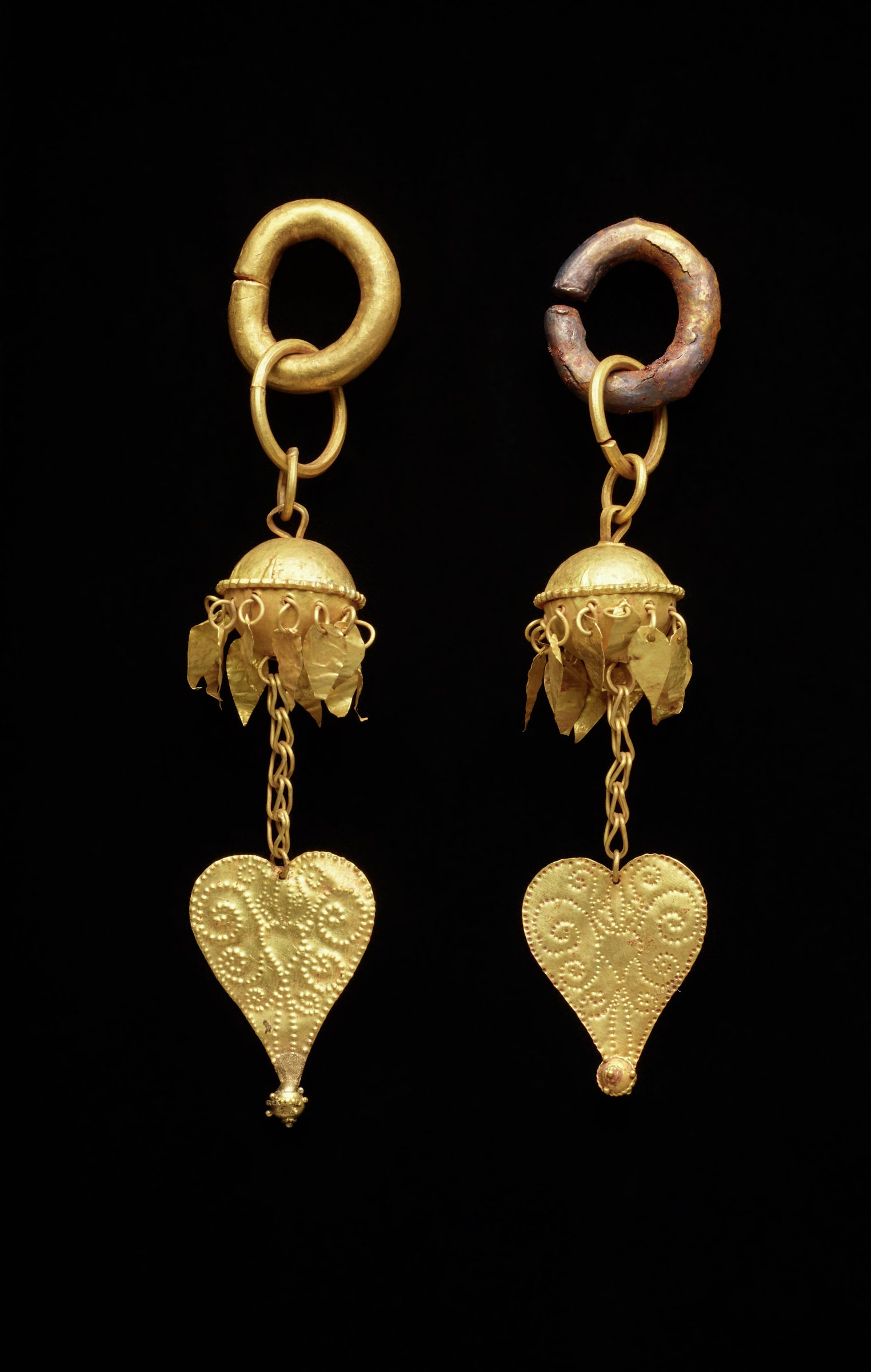 Heavy gold loops that have a slit in them are at the top of the earrings.  The slits would have allowed the wearer to slip them on their earlobes. Gold balls decorated with small gold suspended bangles form the center, with openwork gold heart-shaped pendants at the bottom. Granulation on finials with one finial bent.