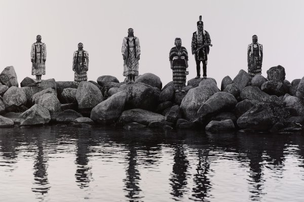 Black and white photograph with six Native American people wearing regalia and face-coverings, standing apart on boulders, water in foreground.
