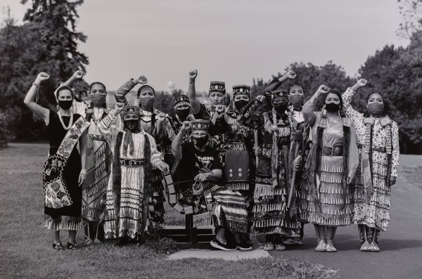 Black and white photograph with twelve Native American people outdoors, wearing regalia and face coverings, each with one fist raised.