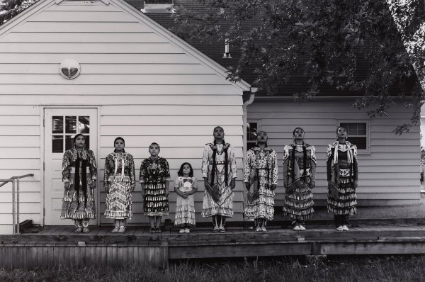 Black and white photograph of eight Native American women and girls wearing jingle dress regalia, standing on outside deck of Mille Lacs trading post.
