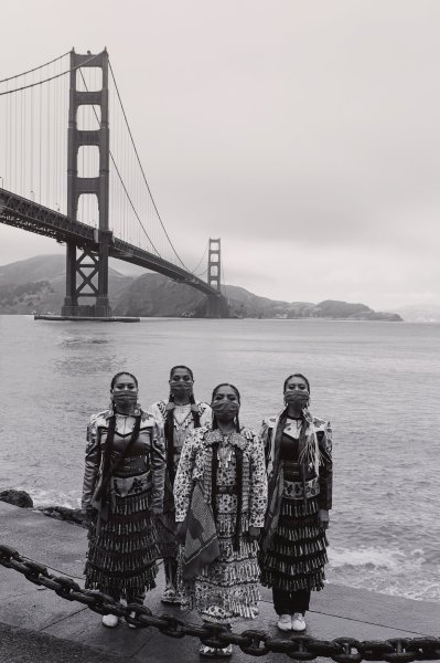 Black and white photograph of four Native American women wearing jingle dress regalia and bandana face-coverings, Golden Gate Bridge in background