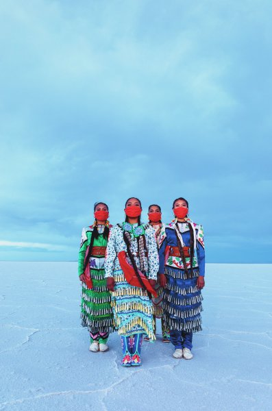 Color photograph with four Native American women wearing jingle dress regalia and red bandana face-coverings, standing at Bonneville Salt Flats, blue cloudy sky in background.