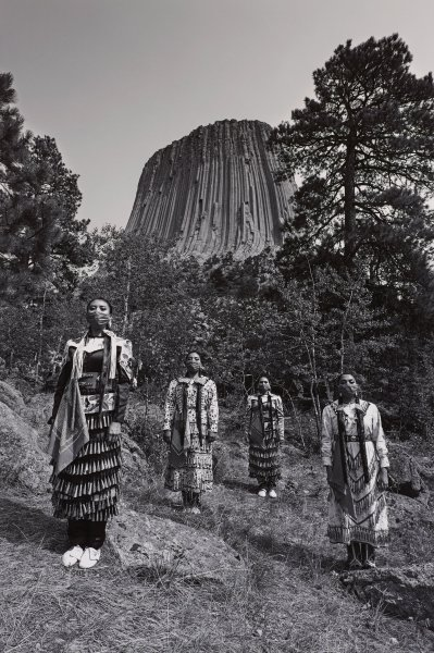 Black and white photograph of four Native American women wearing jingle dress regalia and bandana face-coverings, Bear Medicine Lodge National Monument in background.